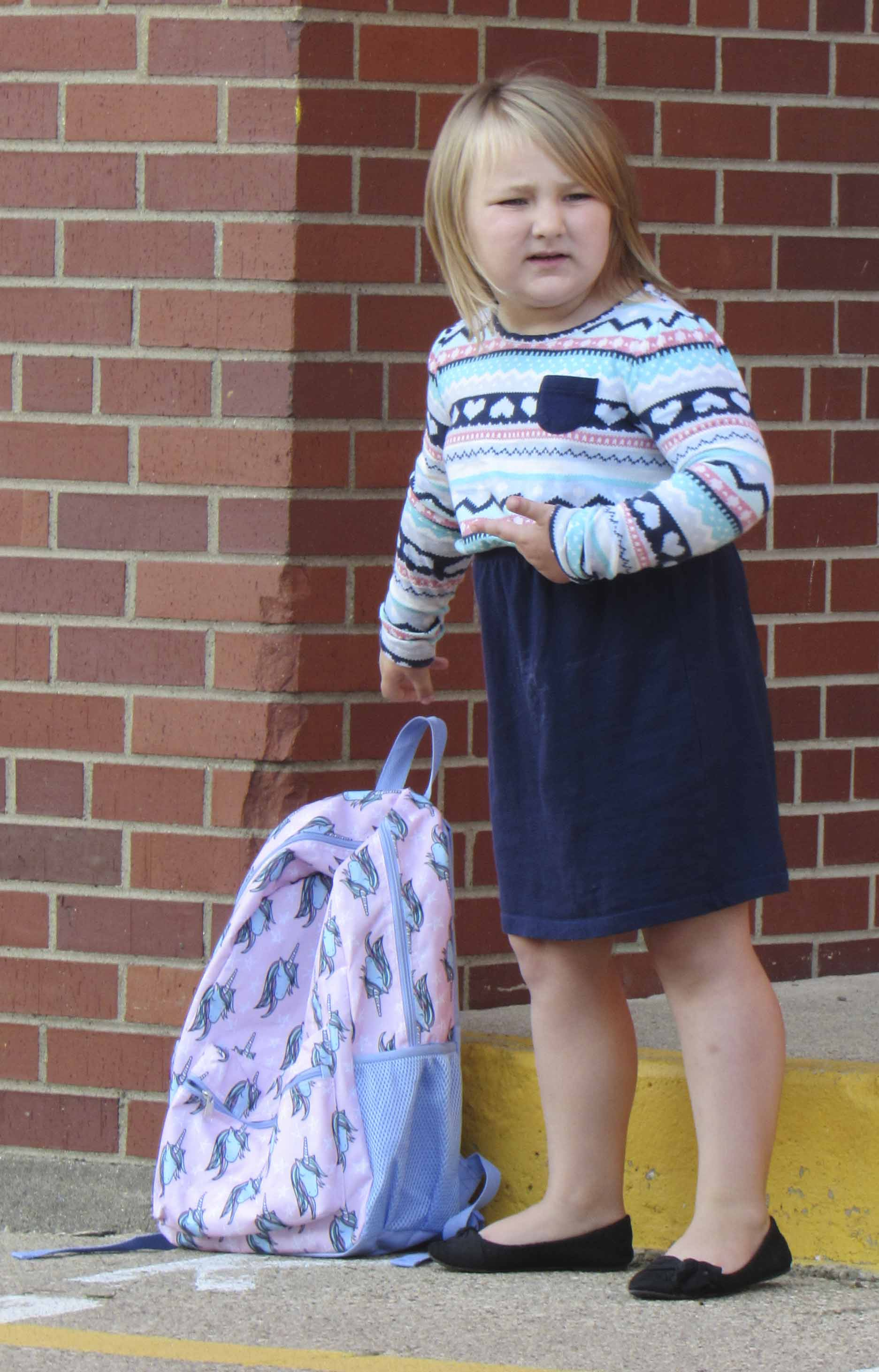 "Sacred Heart kindergartener Elizabeth Oswald looks for the letter ""K"" to reserve her spot in line for her first day of school. (Photo by Kim Brooks)"