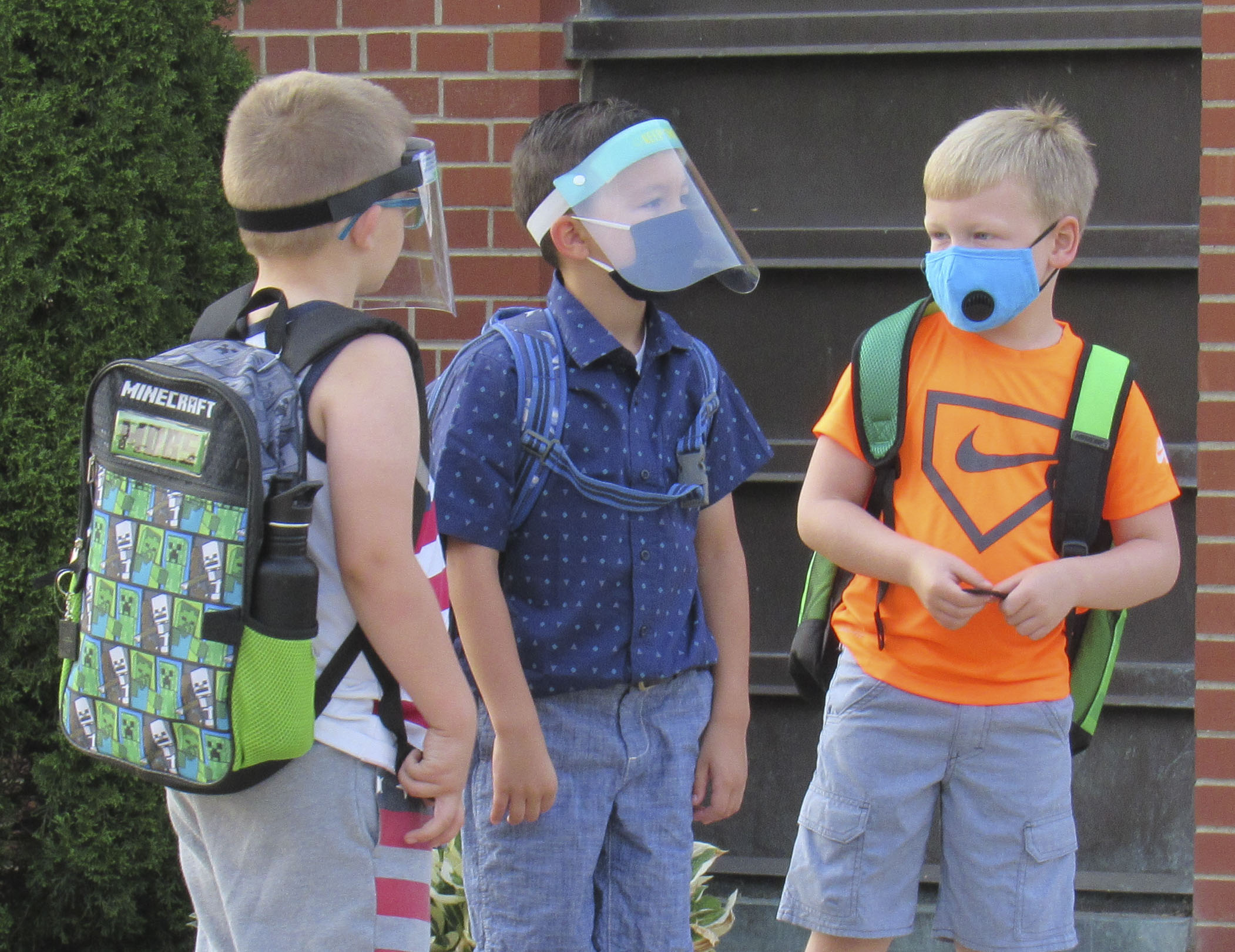 First-graders at Sacred Heart, Lincoln Crawford, David Lyons, and David Intlekofer, join together on the first day of school. Face coverings were a must as students waited in line. (Photo by Kim Brooks)