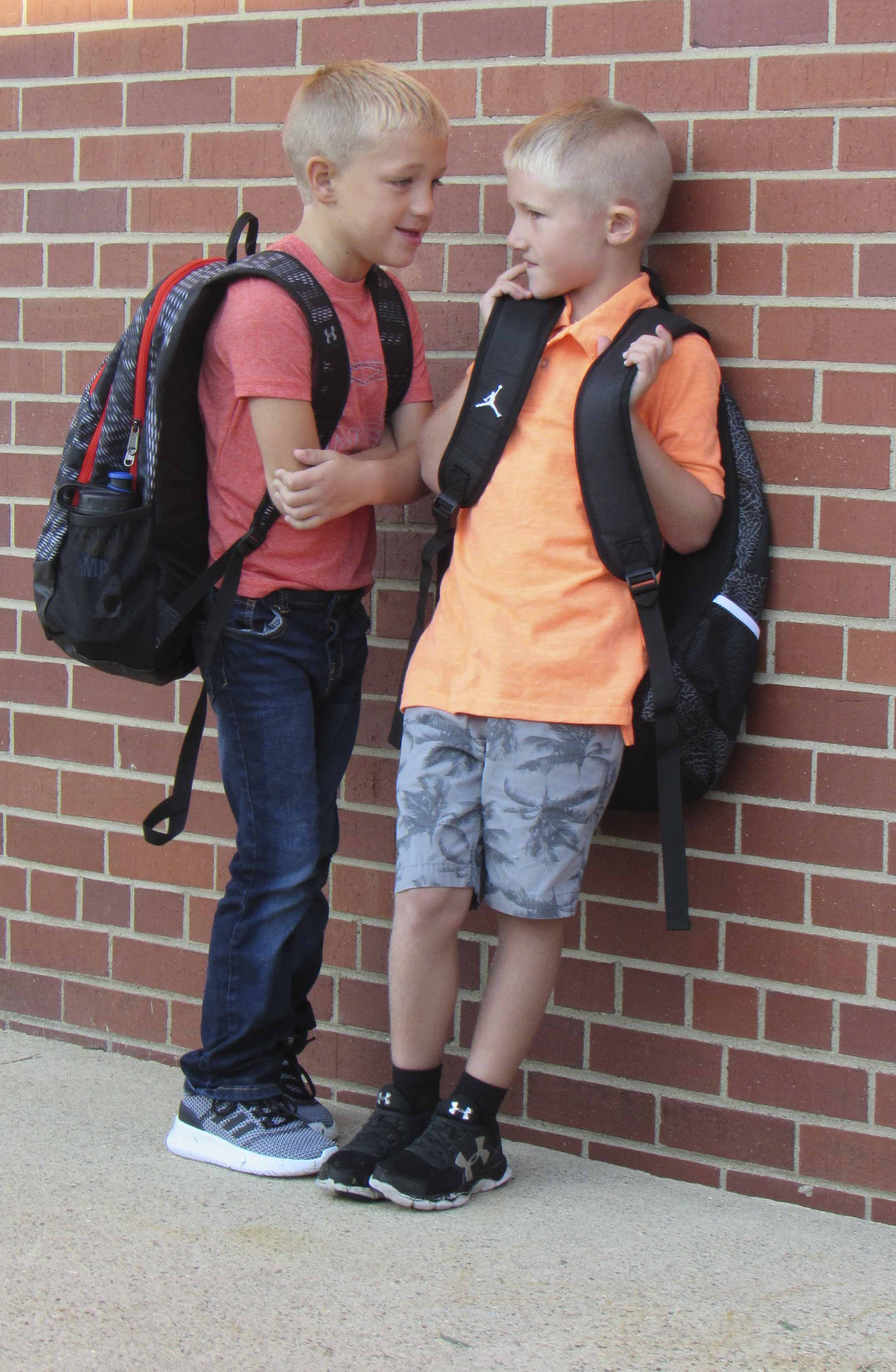 First-grader Nick Schlarmann talks with kindergartener Adler Jacobs as they wait for the bell to ring on the first day of school at Sacred Heart. (Photo by Kim Brooks)