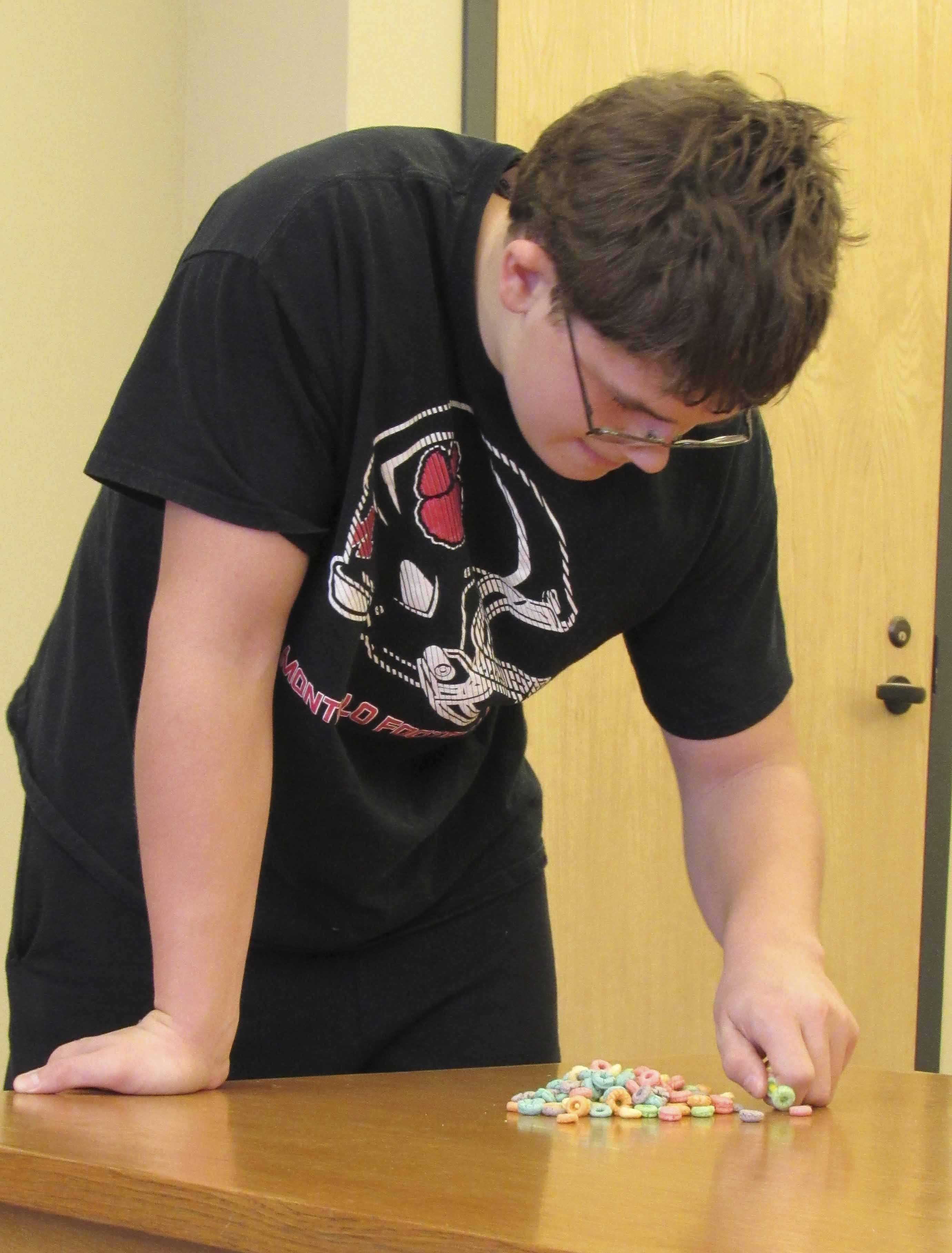 Mason Reuter, 14, tries his hand at a 60-second challenge contest, picking up Fruit Loops with a pipe cleaner using only one hand. Not as easy as it looks.