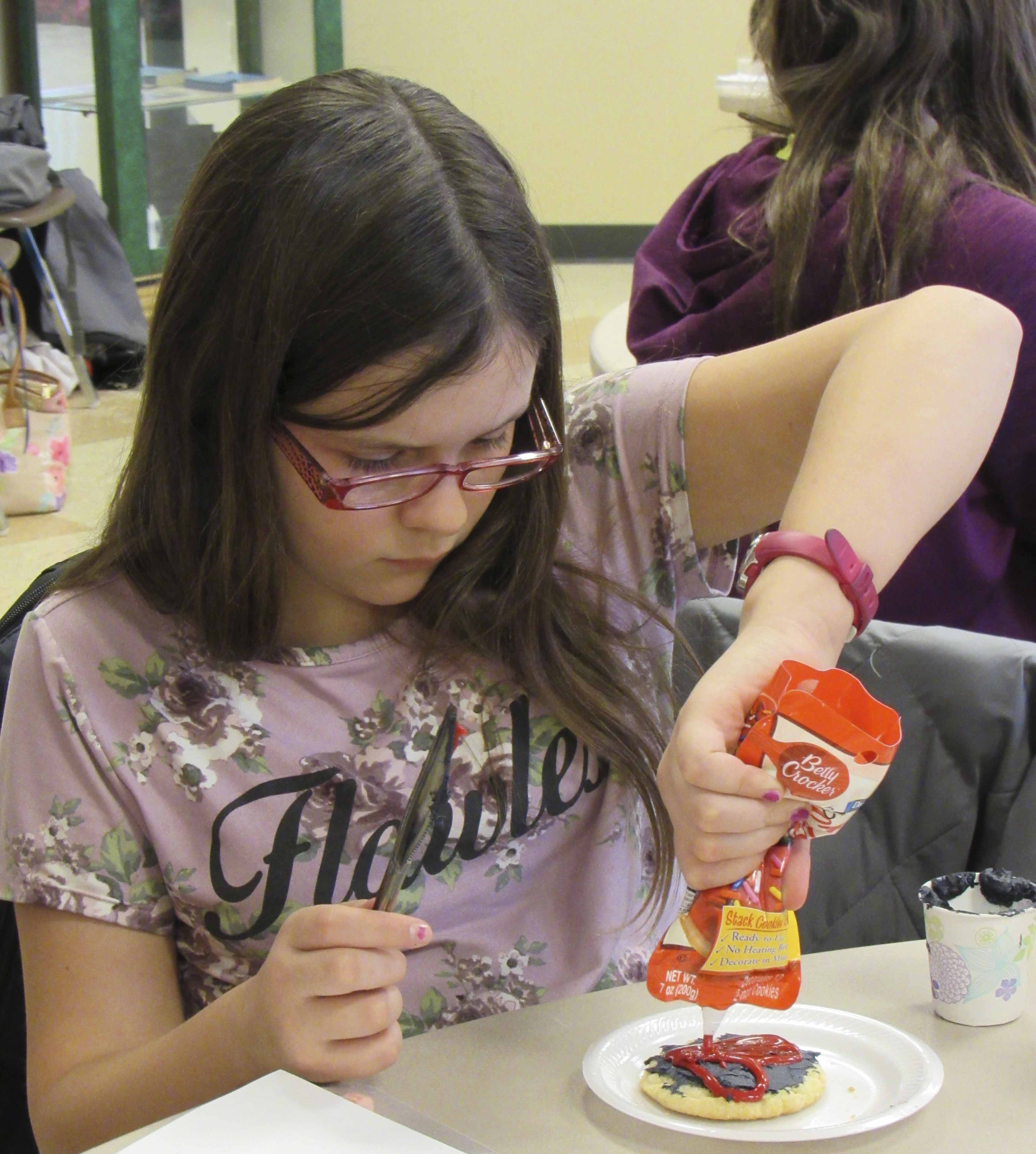 Lexi Gaal works on decorating her black and red heart cookie at the Monticello library's Anti-Valentine's Day party.