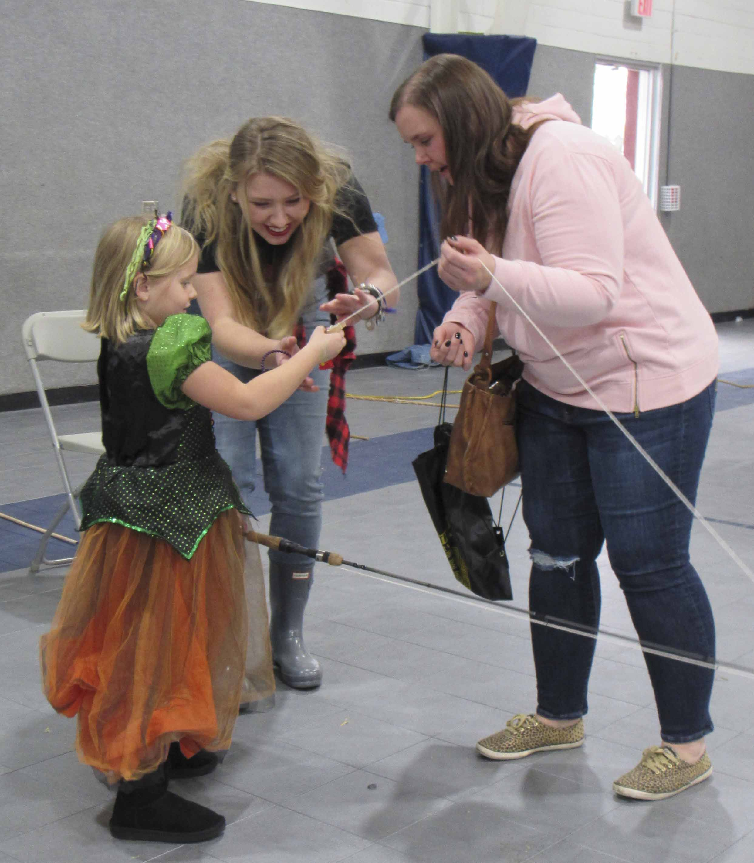Scarlett McDermott looks for her prize at the end of the fishing pole. Assisting at the fishing pond at Austin's Halloween Fun Day to Scare Away Childhood Cancer was Elle Boeding. Also pictured is Scarlett's mom, Kellie McDermott.