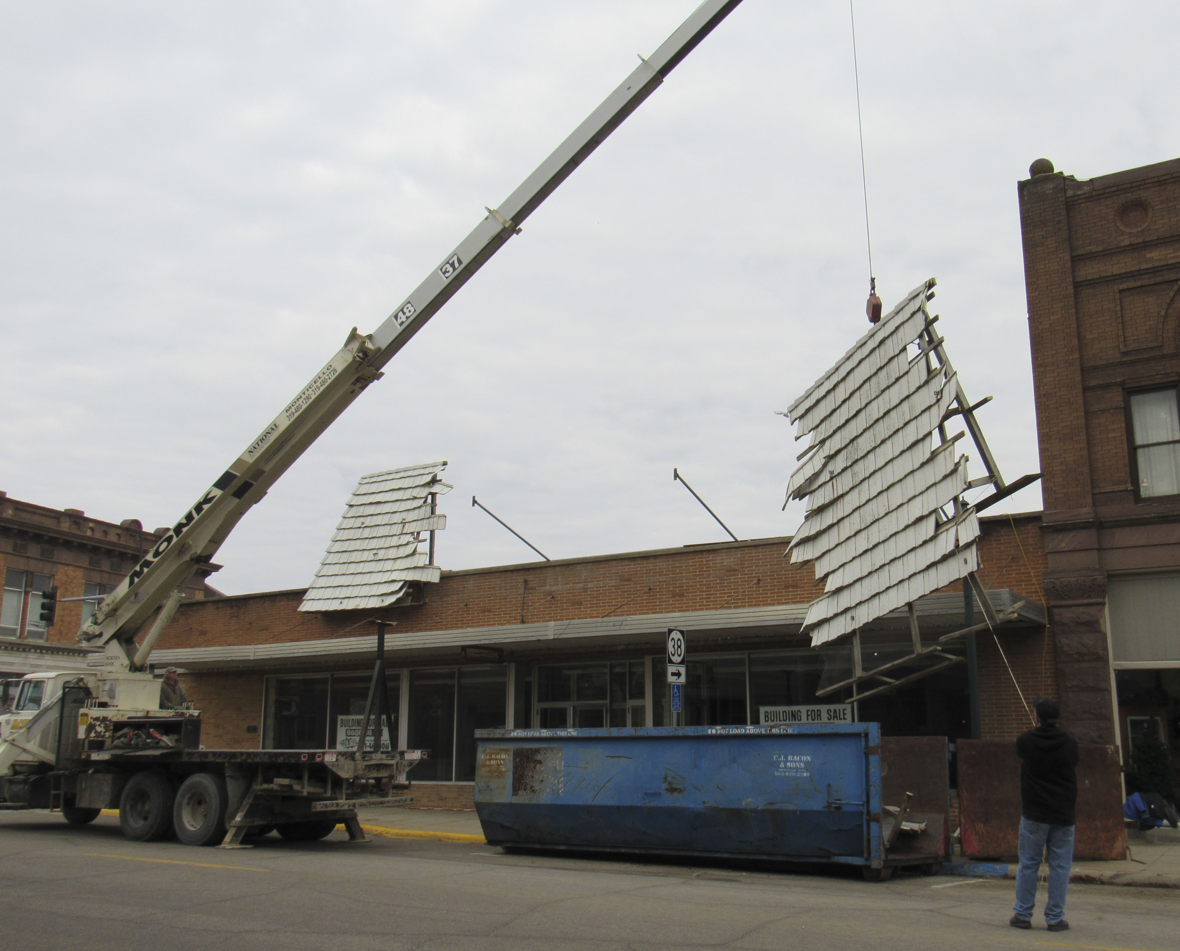 Welter Storage employees were assisted by Monk Construction last week as they tore down the old façade and spruced up the former Dollar General building on E. First Street. The building still remains for sale. (Photo by Kim Brooks)