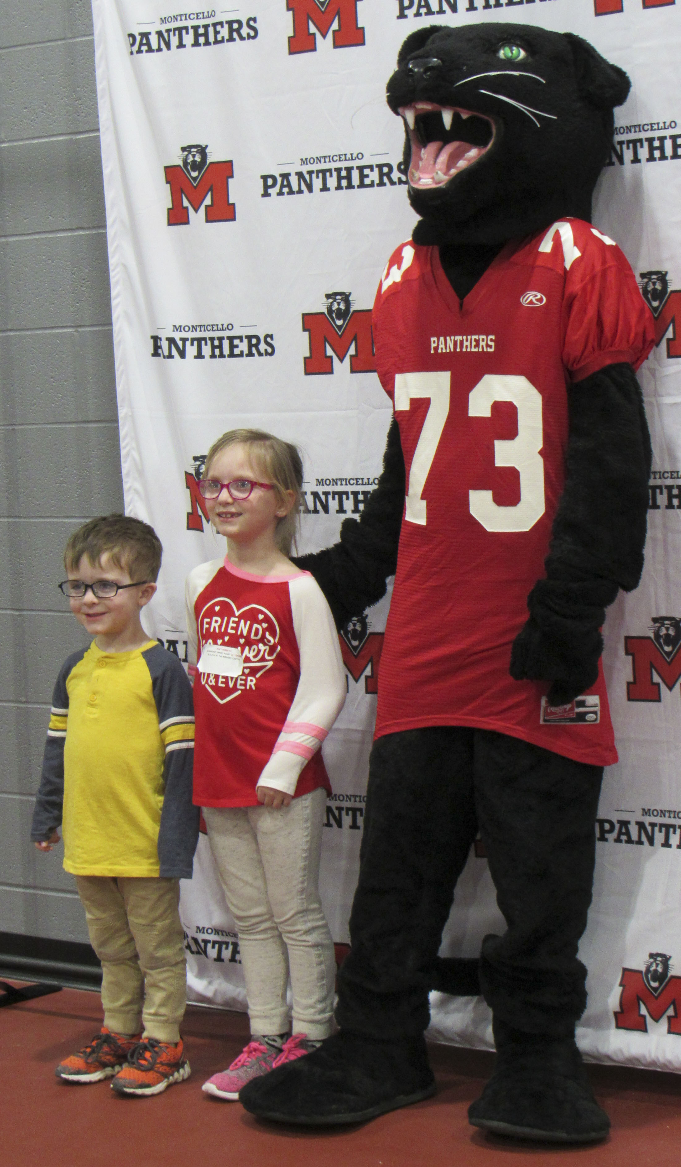 """Siblings Memphis and Roslynne """"Roz"""" Russ pose for a picture with the Monticello School mascot, the Panther. Curriculum Director Gretchen Kriegel took photos of elementary students with the Panther throughout the evening."""