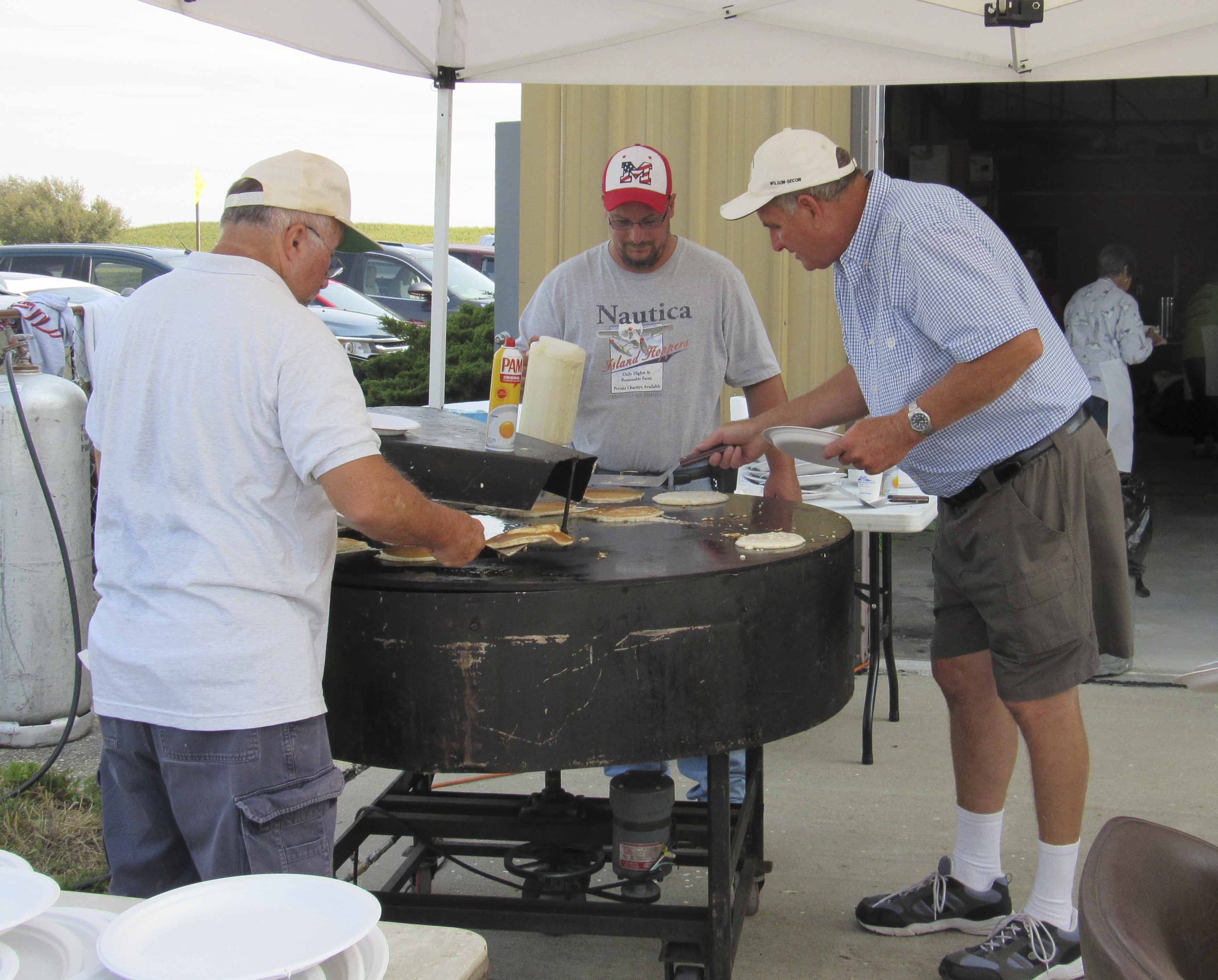 Dick Bartholomew, Mike Bader and Kevin Lynch volunteer at the pancake station for the Monticello airport's Fly-in Breakfast. (Photos by Kim Brooks)