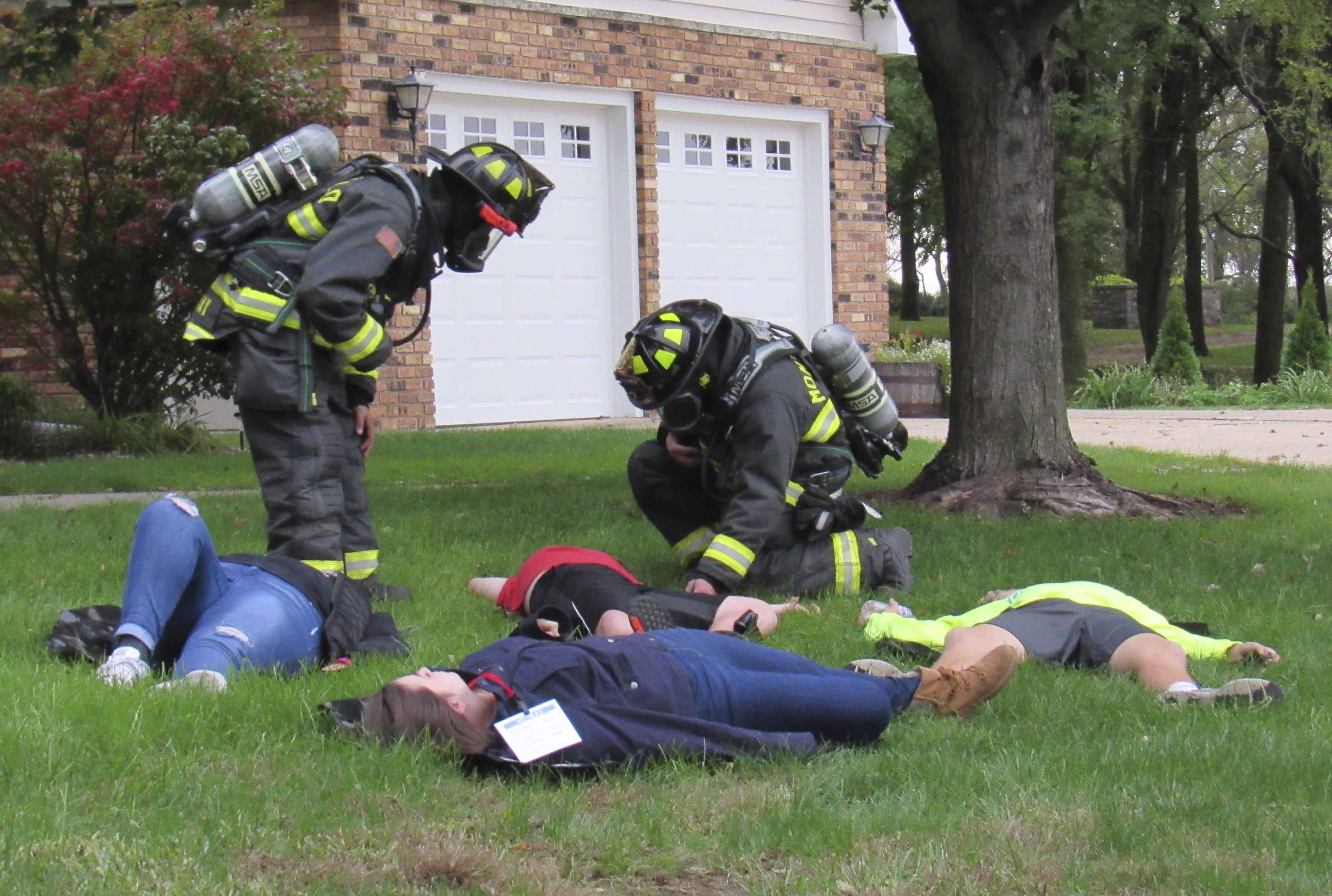 Monticello Firefighters Josh Kray and Nick Spahr inspect the scene of a chemical spill as a family lies on the front lawn of a house on Songbird Lane. On Oct. 2, several public safety agencies from Jones County came together near Monticello High School for a hazmat training exercise. The scenario revolved around a semi truck full of chlorine that overturned on Highway 151. Those who volunteered as the family members include Olivia Goodyear, Keegan Freese, Grahm Schneiter, and Allison Leonard.