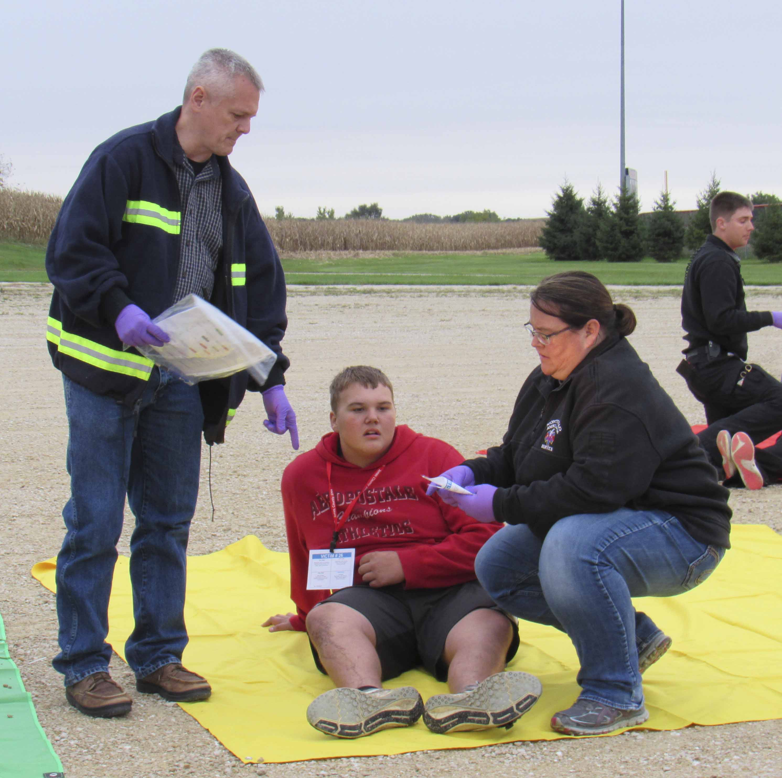 Several paramedics and EMTs took part in the training. Several high school students also volunteered their time to take on various victim roles. Here, Chris Bell and Mandy Norton tend to Kaden Kiburz who was on the soccer field during the chemical spill. (Photos by Kim Brooks)