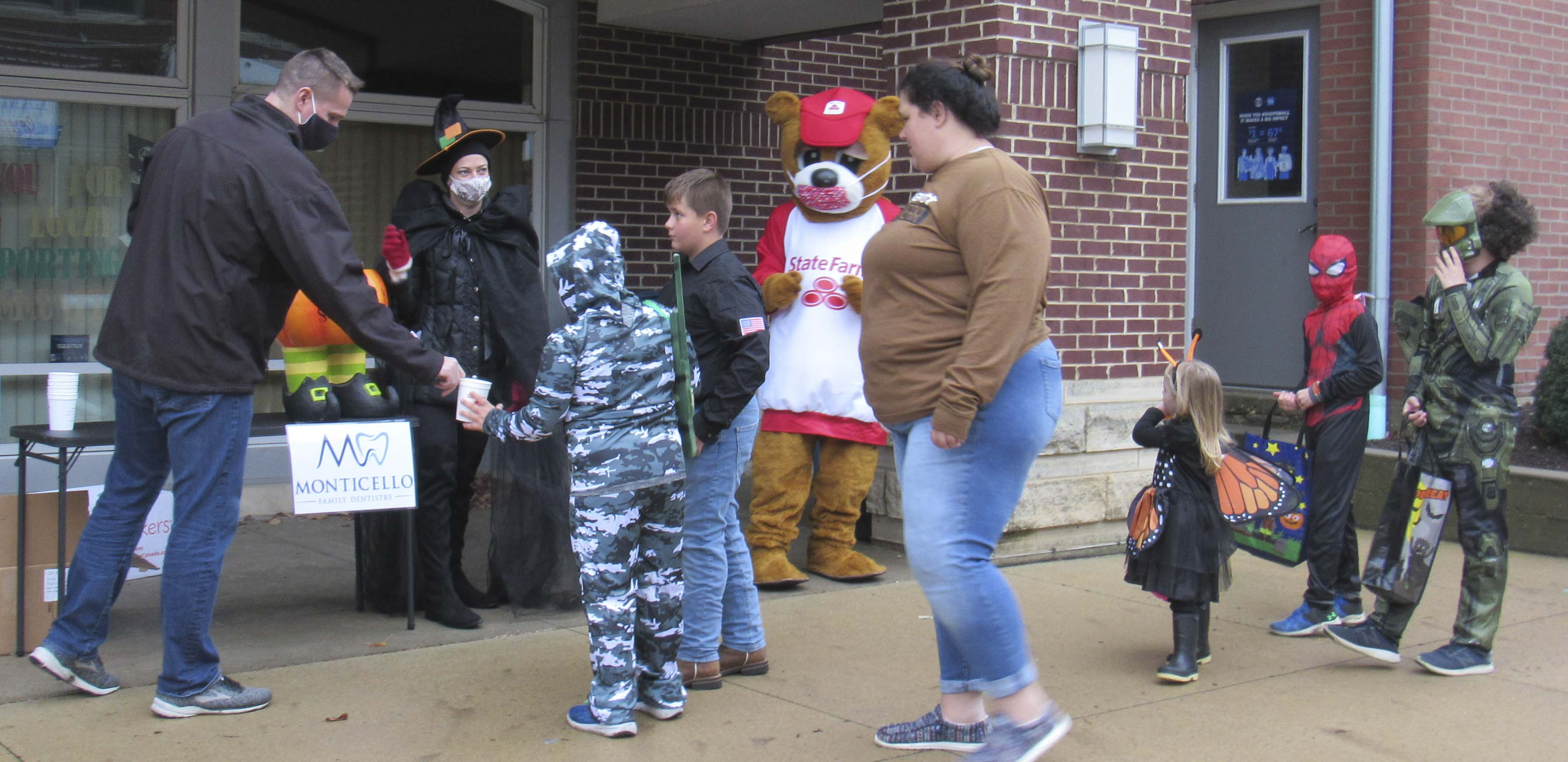 Rick Meyer with State Farm and Dr. Lindsey Meyer with Monticello Family Dentistry hand out candy and hot chocolate to kids and parents. The State Farm Good Neighbear also greeted kids, making sure he wore a facemask.