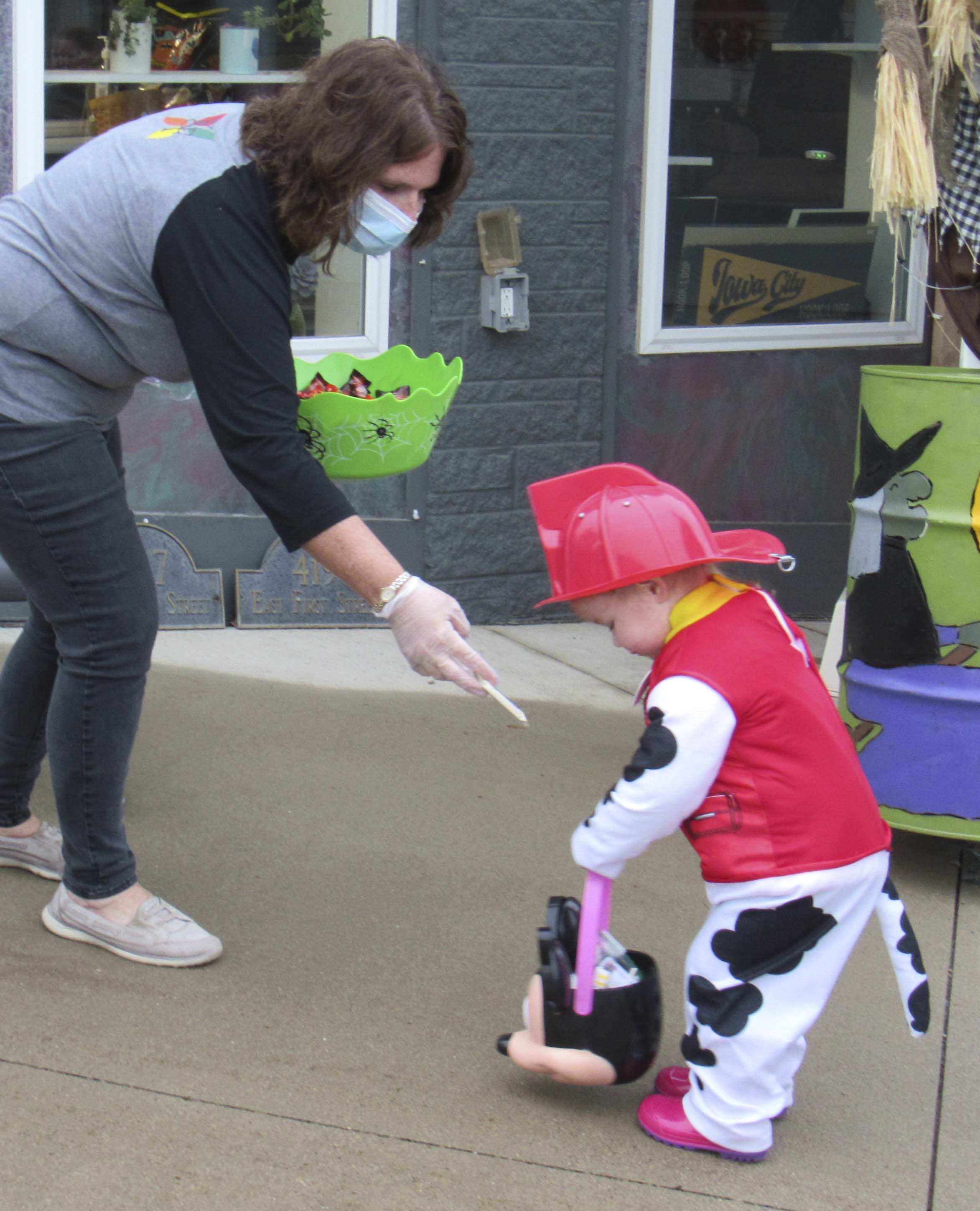 Terri Takes-Tallman, with Advantage Home Medical, hands out candy and hand sanitizer to Aubrey Houdek during Treats on the Streets.