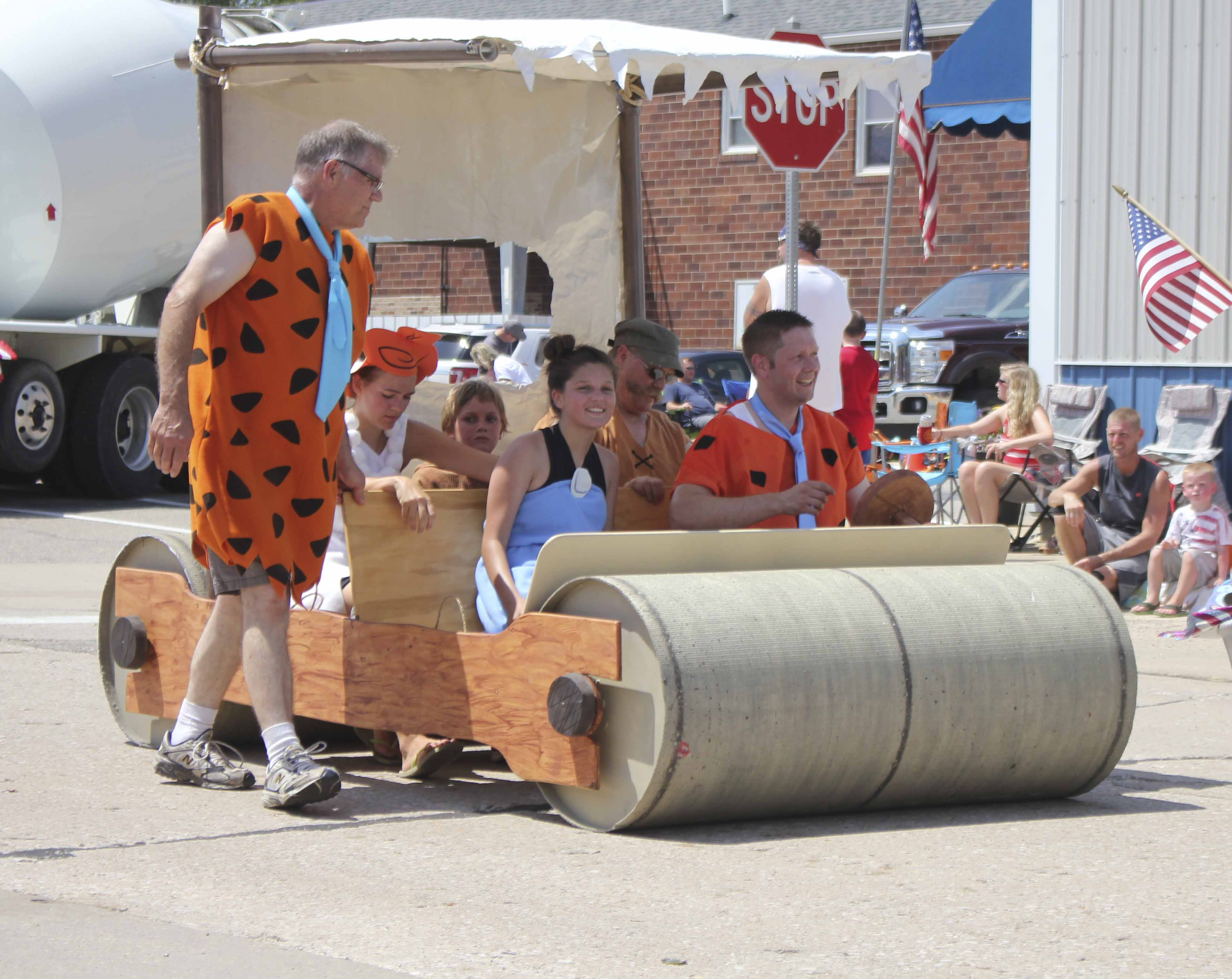 The Schuster family posed as the Flintstones during the Fourth of July Parade. Among them, standing at left: Peter Schuster. Seated in front are (from left) Grace and Andy Schuster. Seated in the back are Sophia, Roman and Paul Schuster.