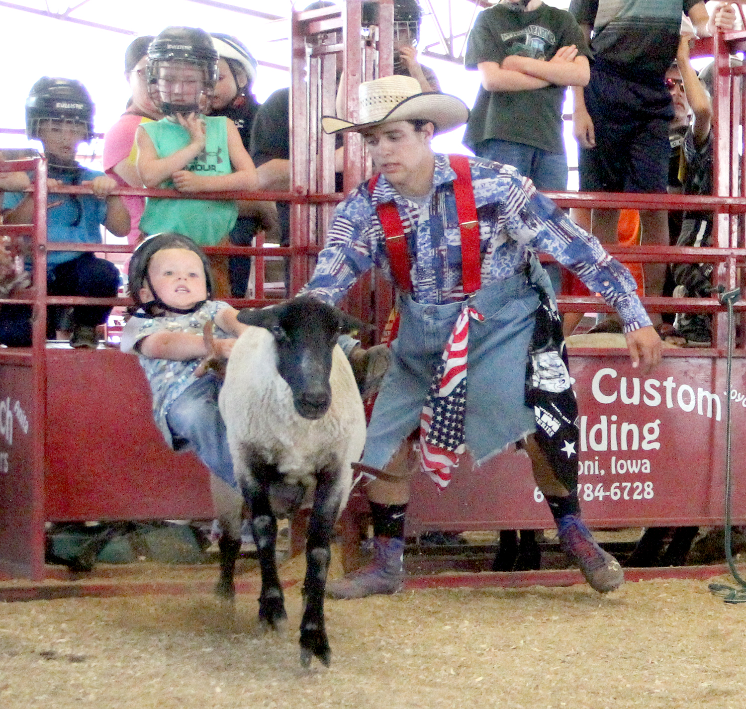 Luke Hosch of Cascade, age 3, hangs on for dear life during the Great Jones County Fair Mutton Busting Contest July 23 at the fairgrounds in Monticello. Be sure to check out coverage of the fair's 4-H, FFA and Open Exhibit show results in Sections B and C. (Photo by Abby Manternach)