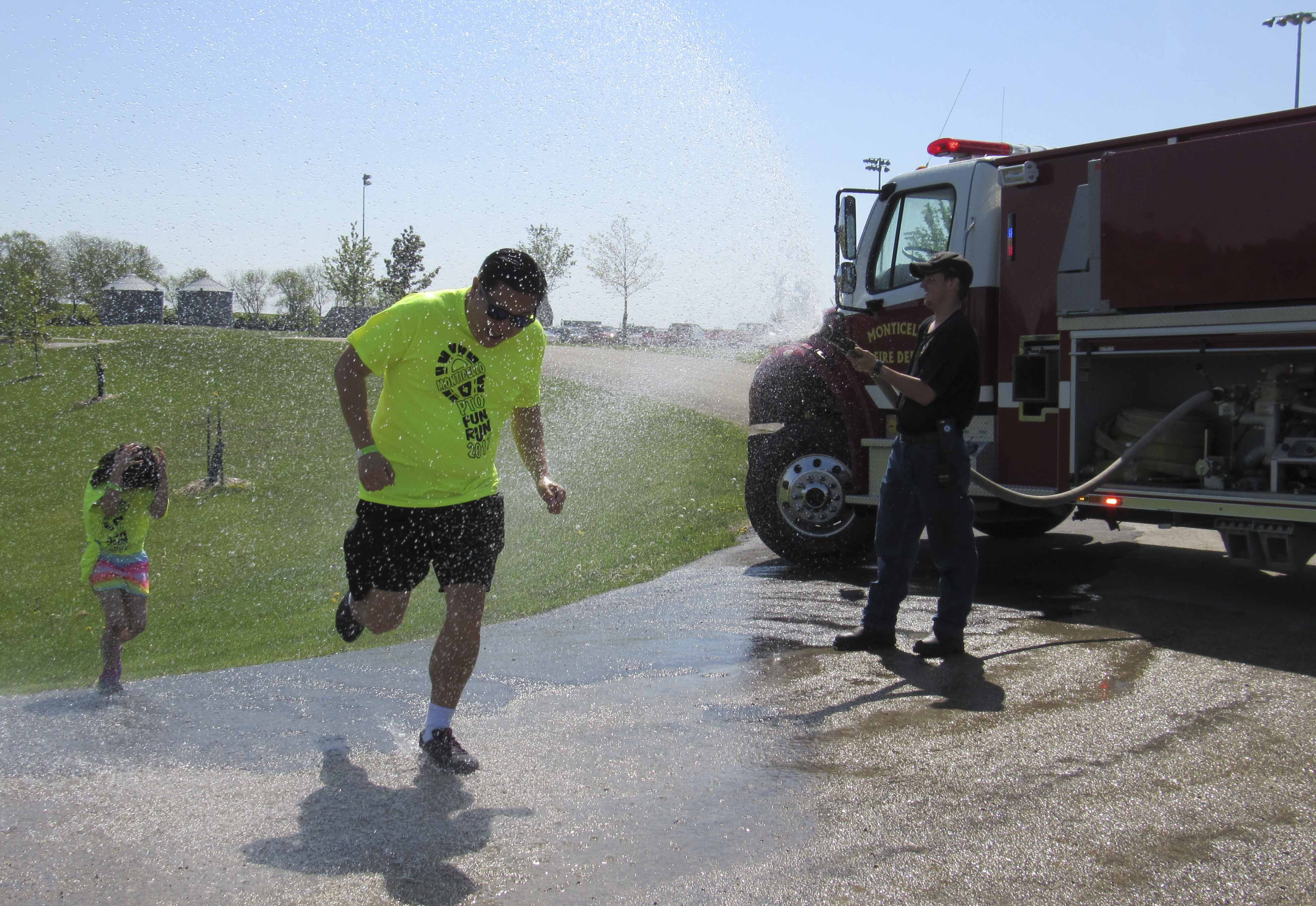 Father and daughter Dave and Kira Lee run through the water station at the PTO Fun Run. The water hose was provided courtesy of the Monticello Fire Department, run by Billy Norton and Tommy Norton.