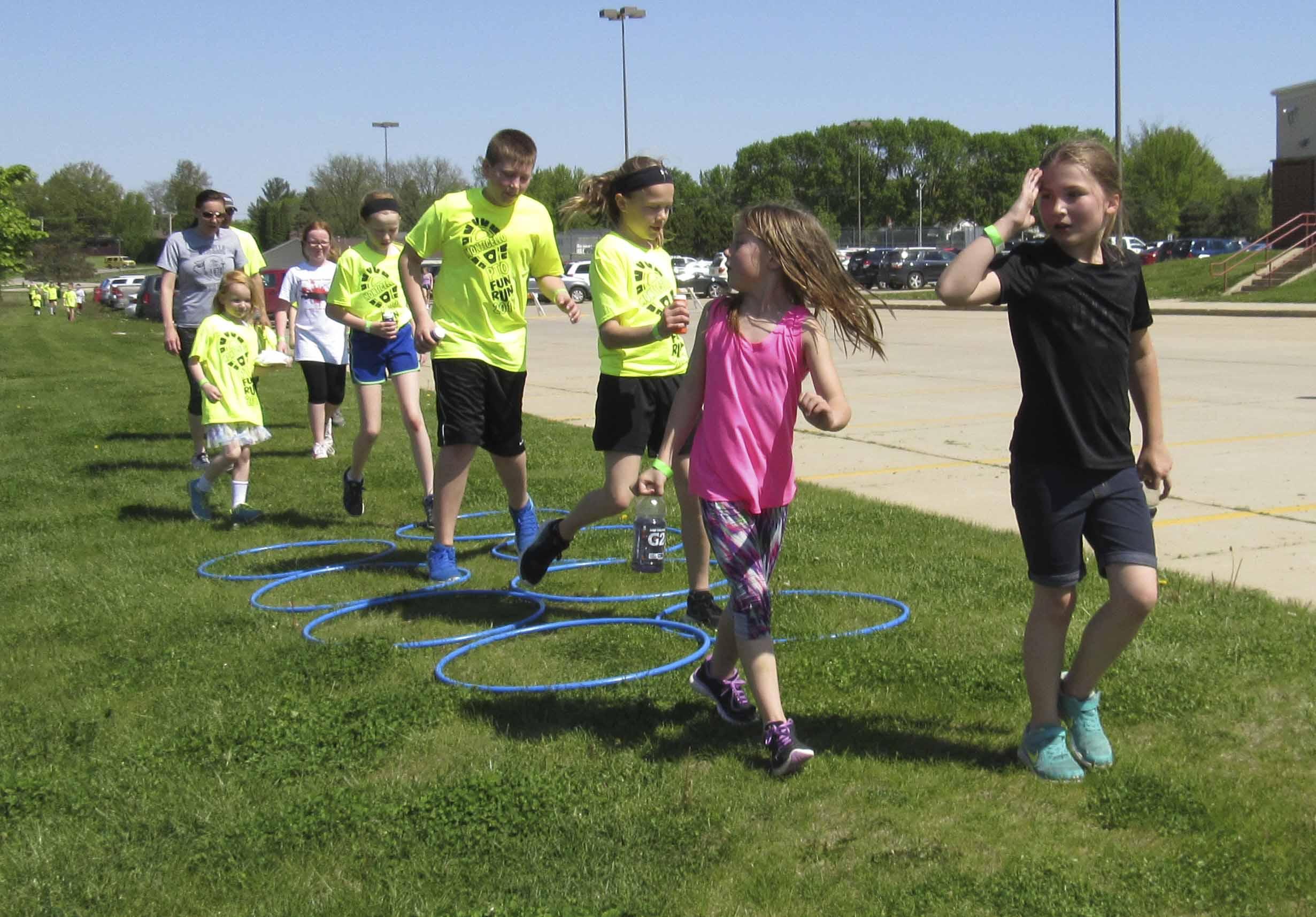 Kids jump through the final hula-hoop hurdle at the PTO Fun Run, May 13. After the run, families enjoyed a dance party and food.