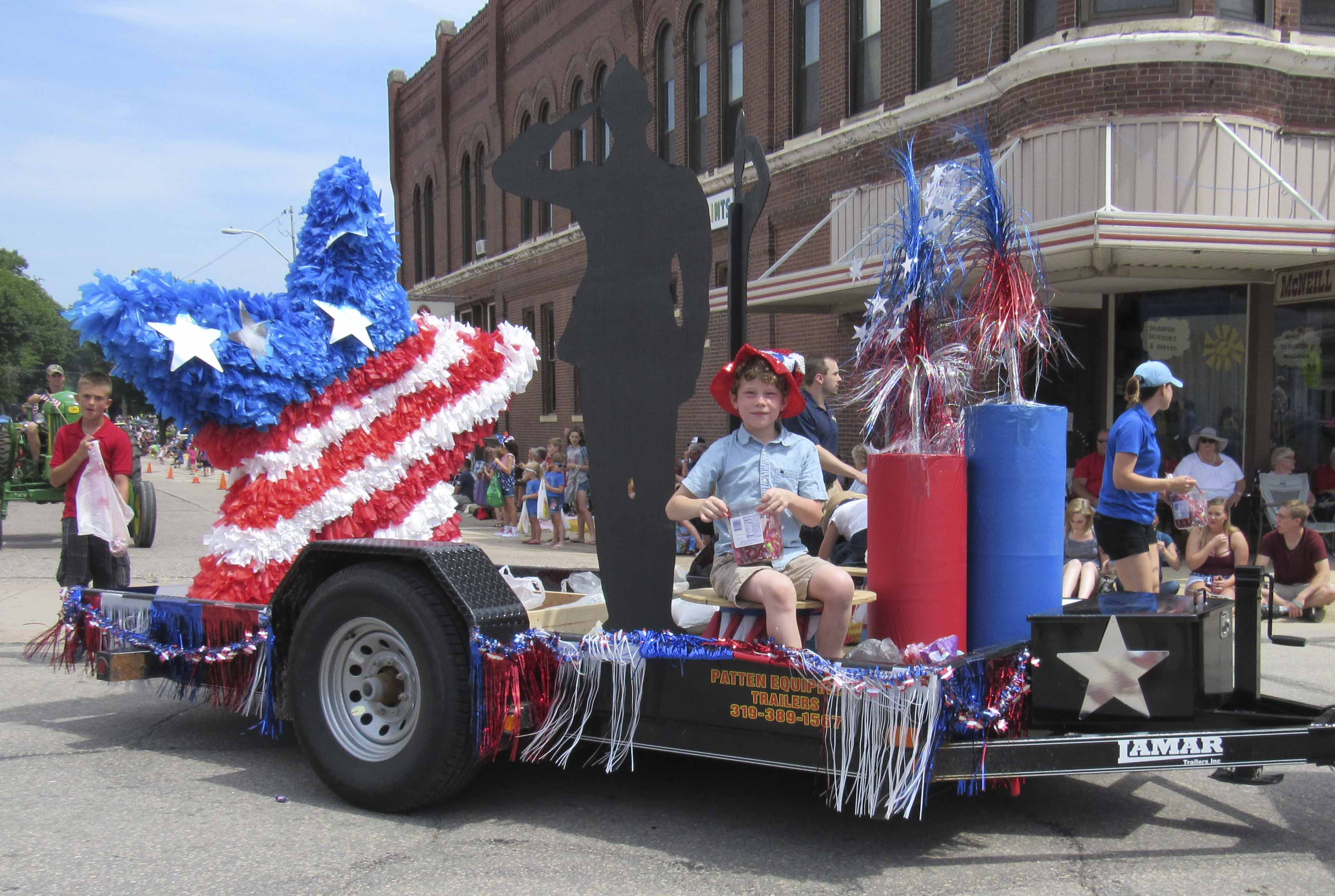 ITS (Infrastructure Technology Solutions) won first place in the Monticello parade. Aedan Althoff, son of ITS owners Leslie and Joel Althoff, throws out candy on the float. (Photo by Kim Brooks)