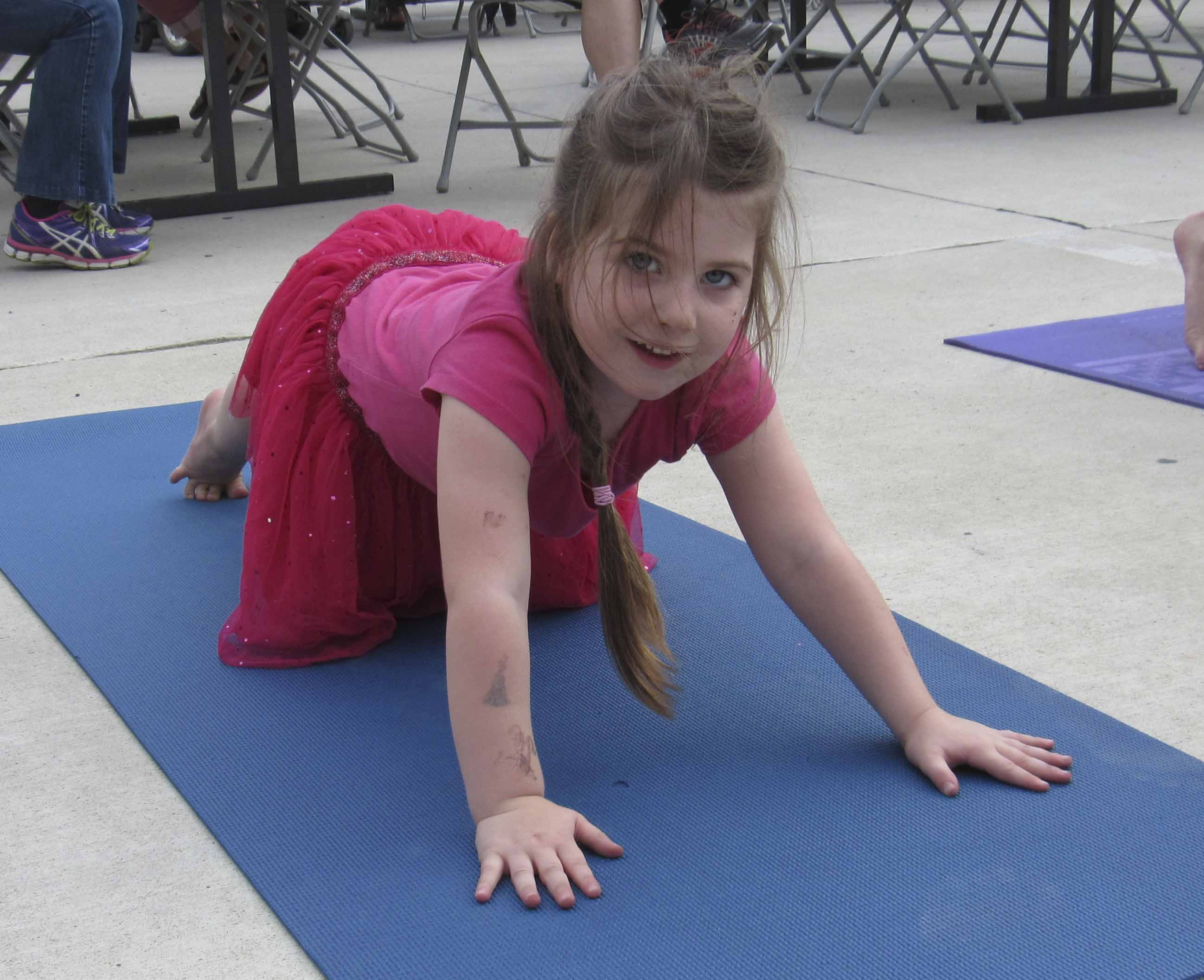 Otillie Farrowe tries her hand at yoga poses during Uptown Thursday Night, Aug. 17.