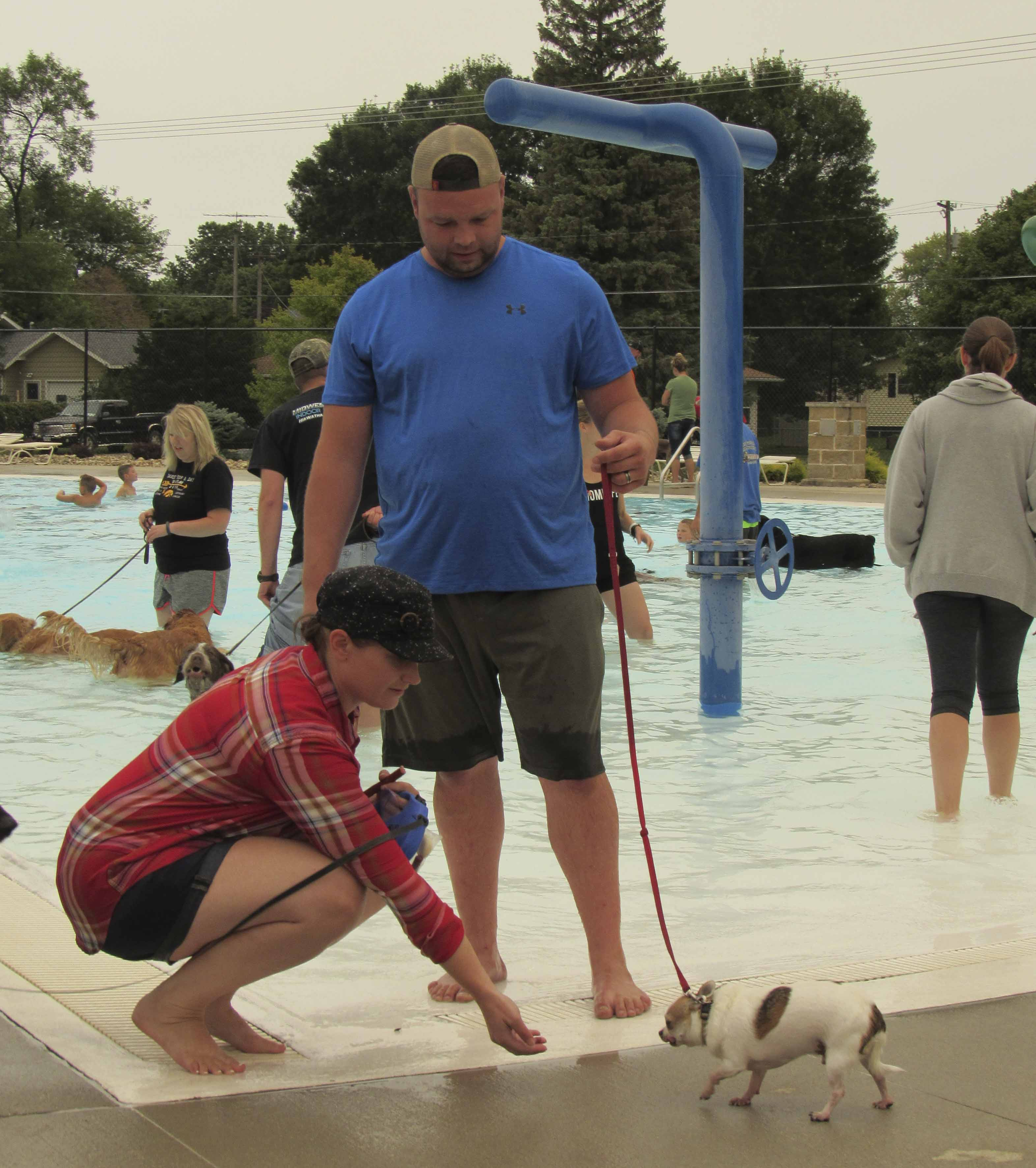 JC and Lindsey Jensen of Monticello ease their dog Tank into the water at the Monticello Aquatic Center. On Sept. 4, Parks and Rec hosted an end-of-summer swimming party for local dogs and their owners. (Photo by Kim Brooks)
