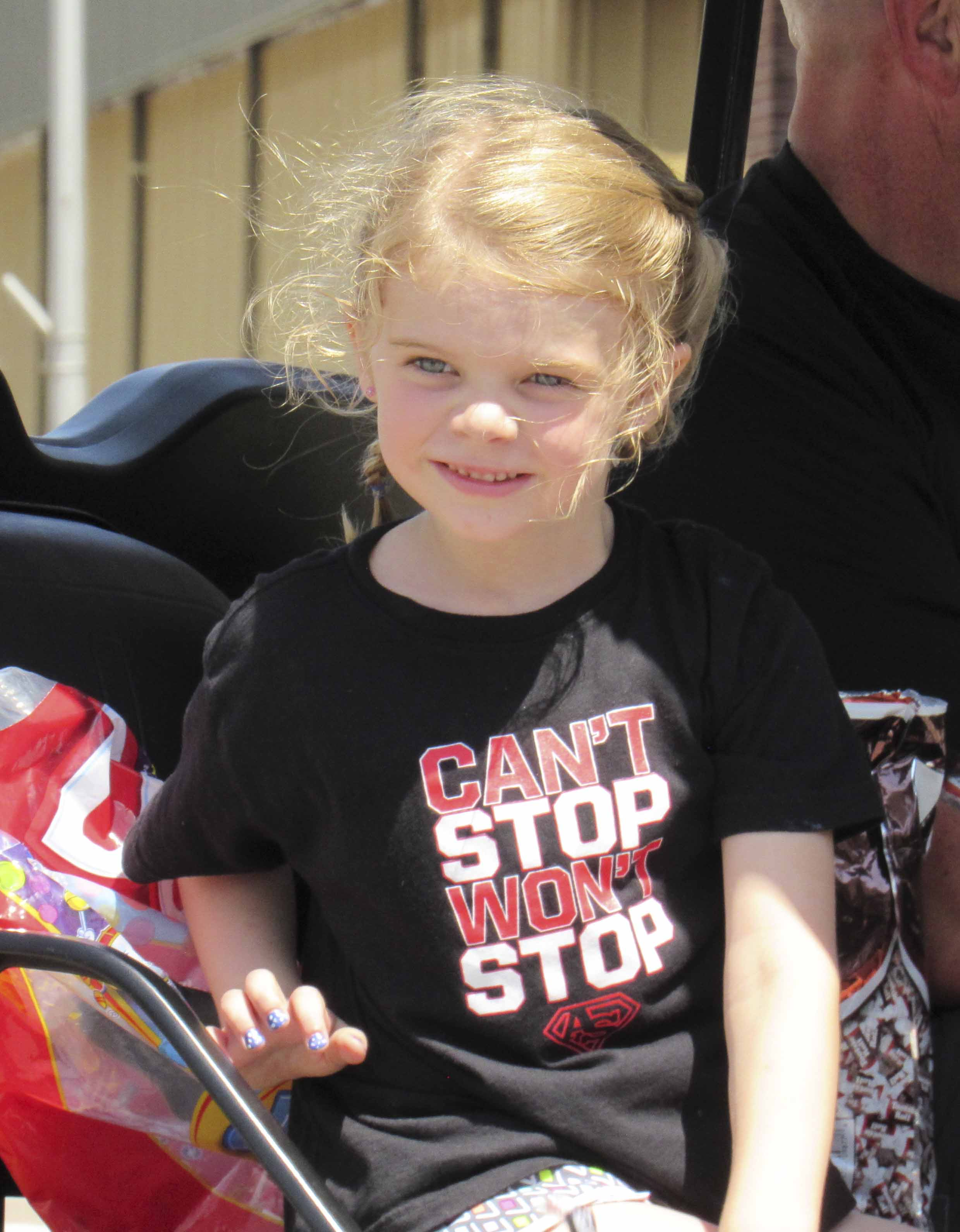 Kennedi McNally helped support the Austin Strong Foundation in the parade, as Jeff Weers drives the gator.