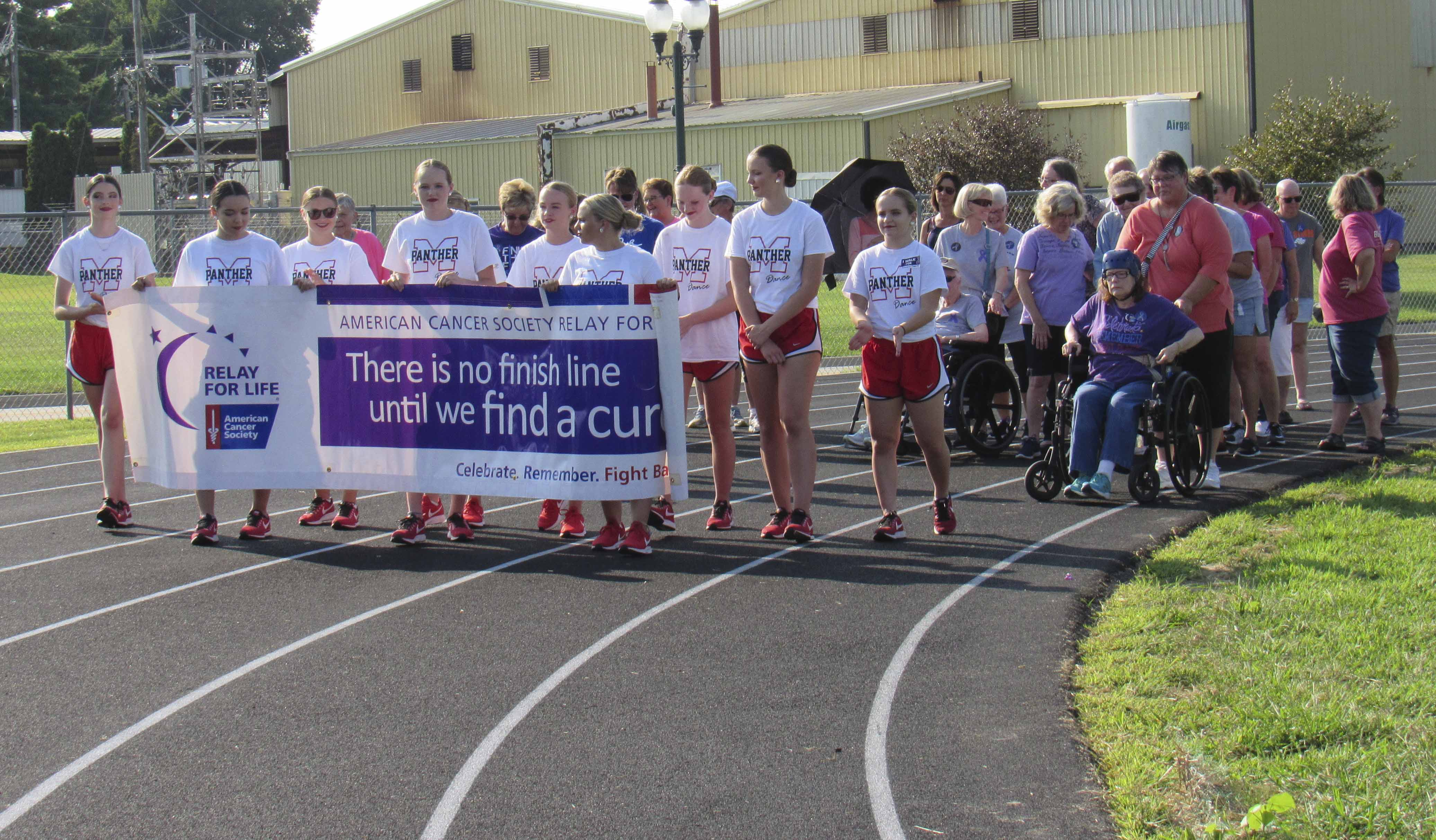 Cancer survivors take the first lap of the RFL of Jones County as the Almost Famous dance girls lead the way with the RFL banner.