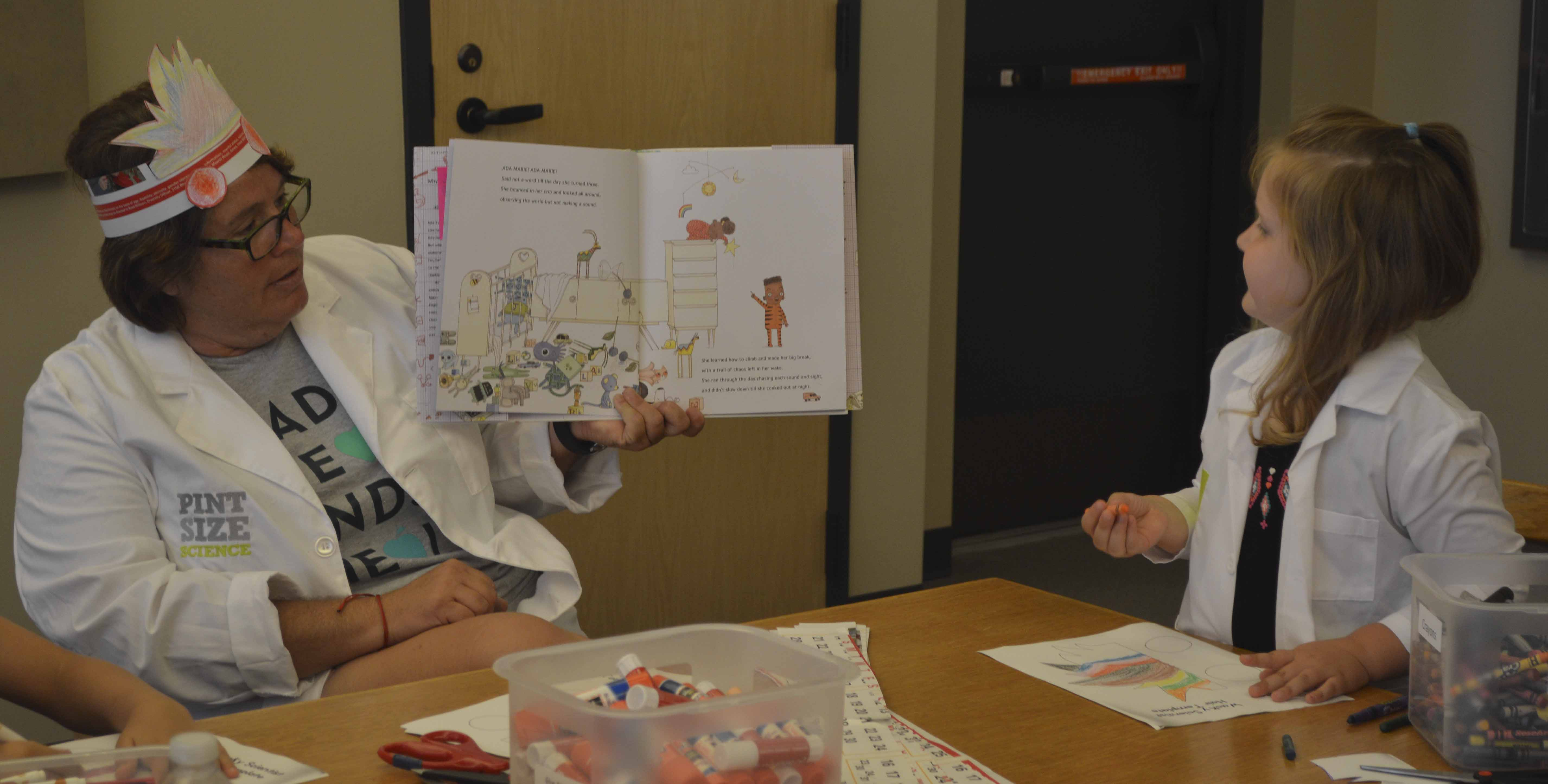 "On Tuesday, June 19, the Monticello Public Library held a science program for youth to participate in. ""Scientist"" Jennifer Fischer (left) read a book to the group, including Holly Morgan who posed as the scientist's assistant."