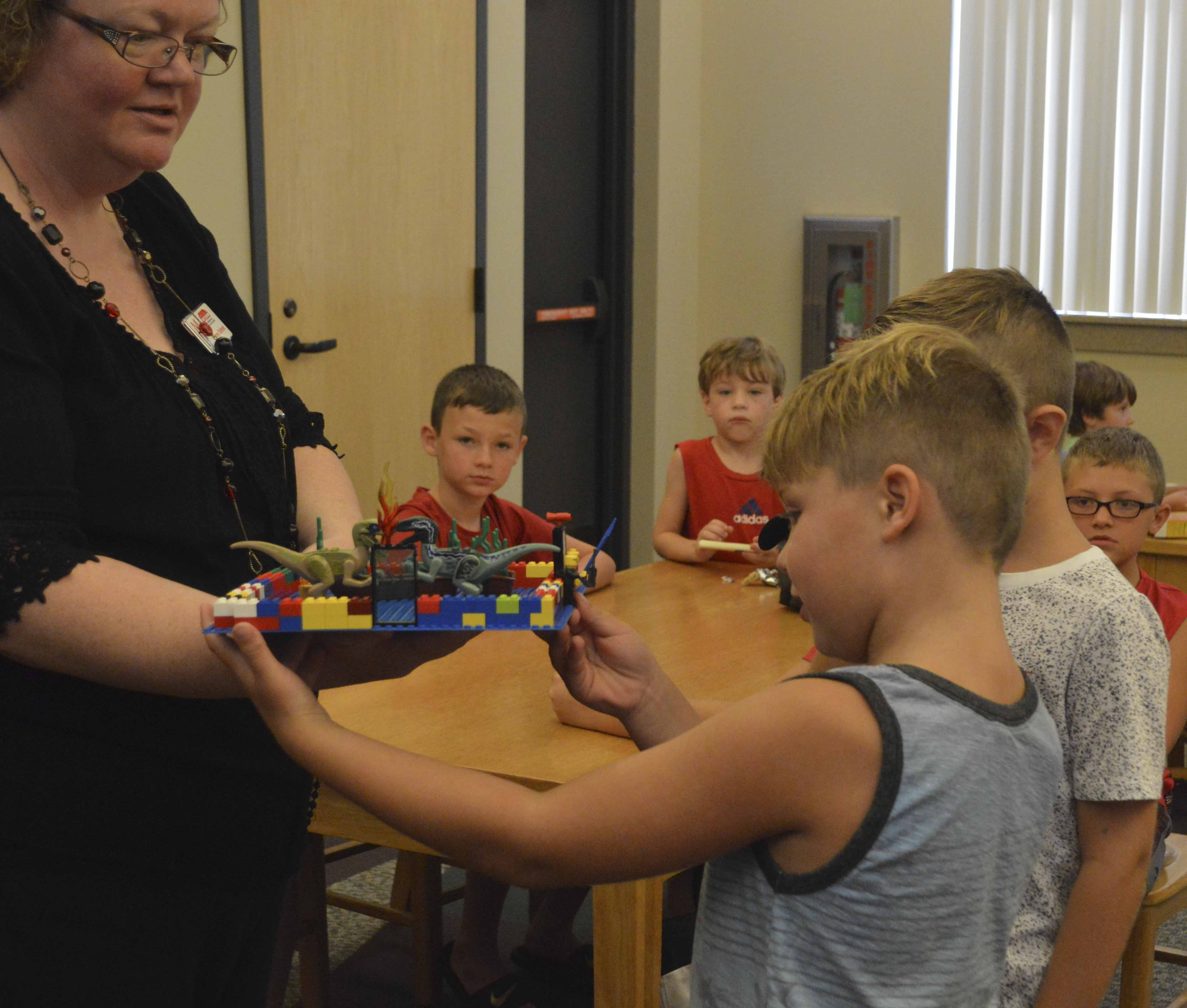 Tate Smith, 8, (front) and Sawyer Adams, 7, explain what their LEGOs represent at the Lunch Bunch Building activity at the Monticello Library on July 26. (Photos by Hannah Gray)