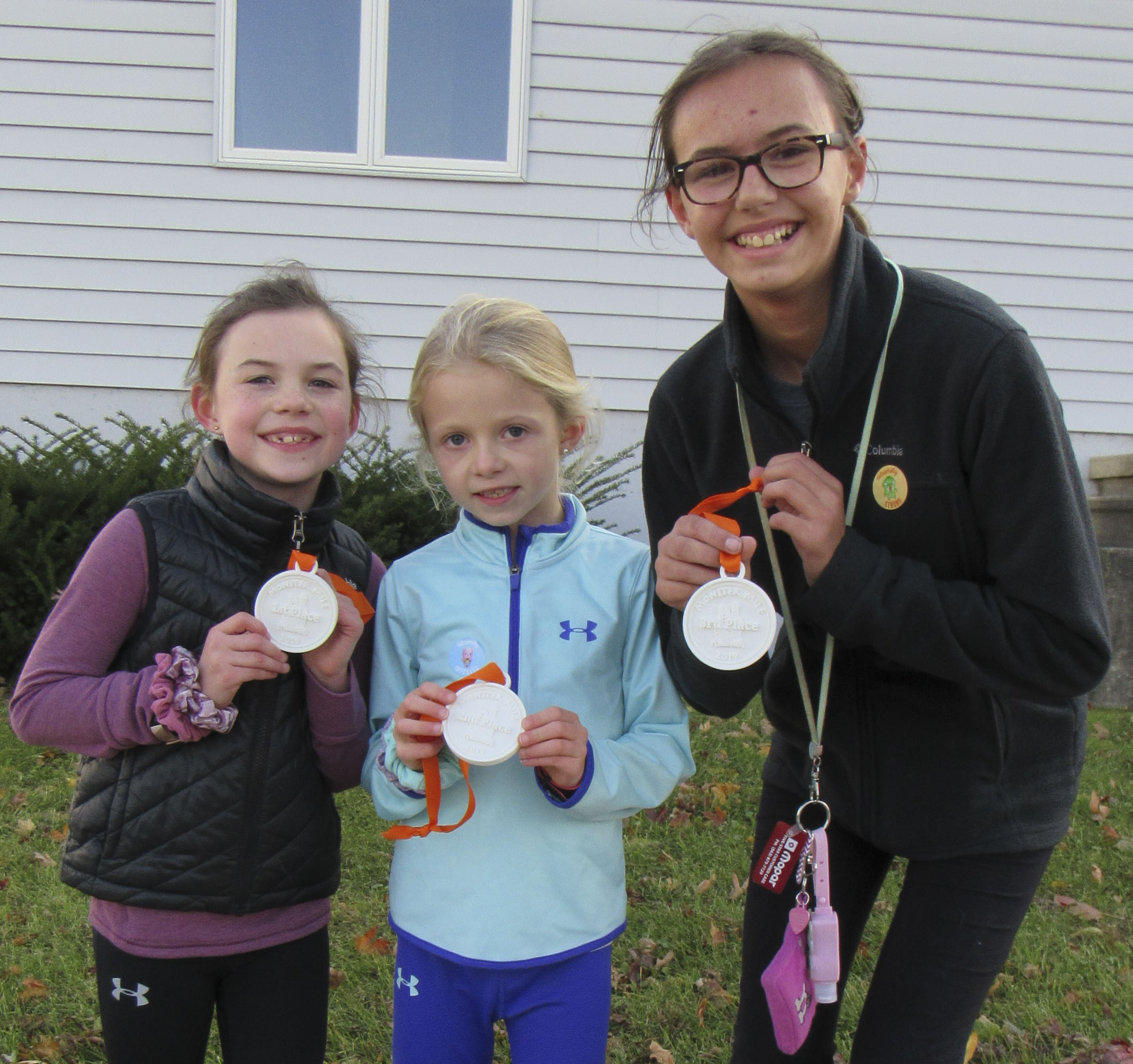 The top three female finishers of the Monster Mile/ Dash were, from left, Julia Ries, Rielle Henderson, and Nevaeh Norton.