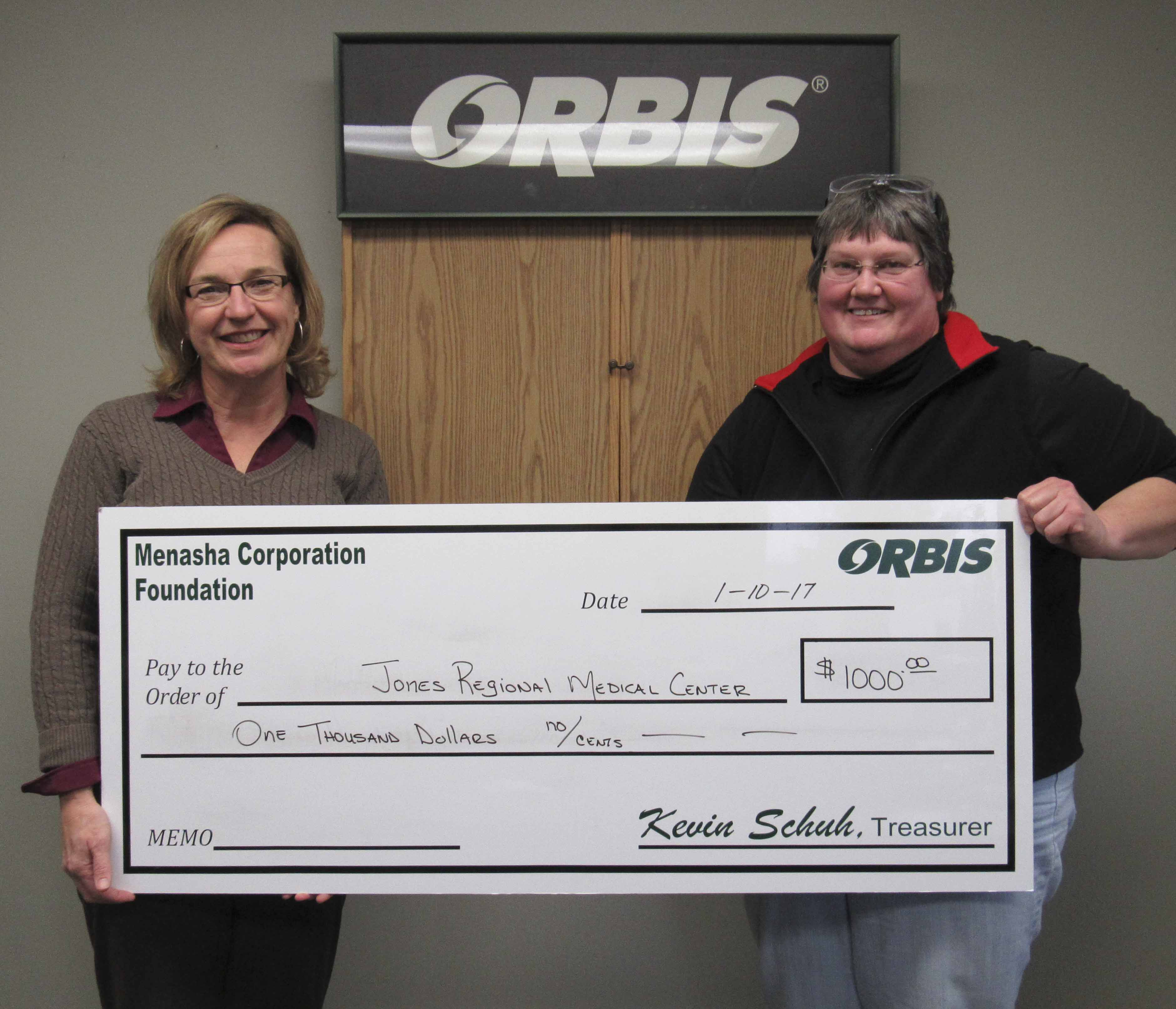 Sheila Tjaden (left) with Jones Regional Medical Center accepts a donation for $1,000 from Cheri Tholen with Orbis.
