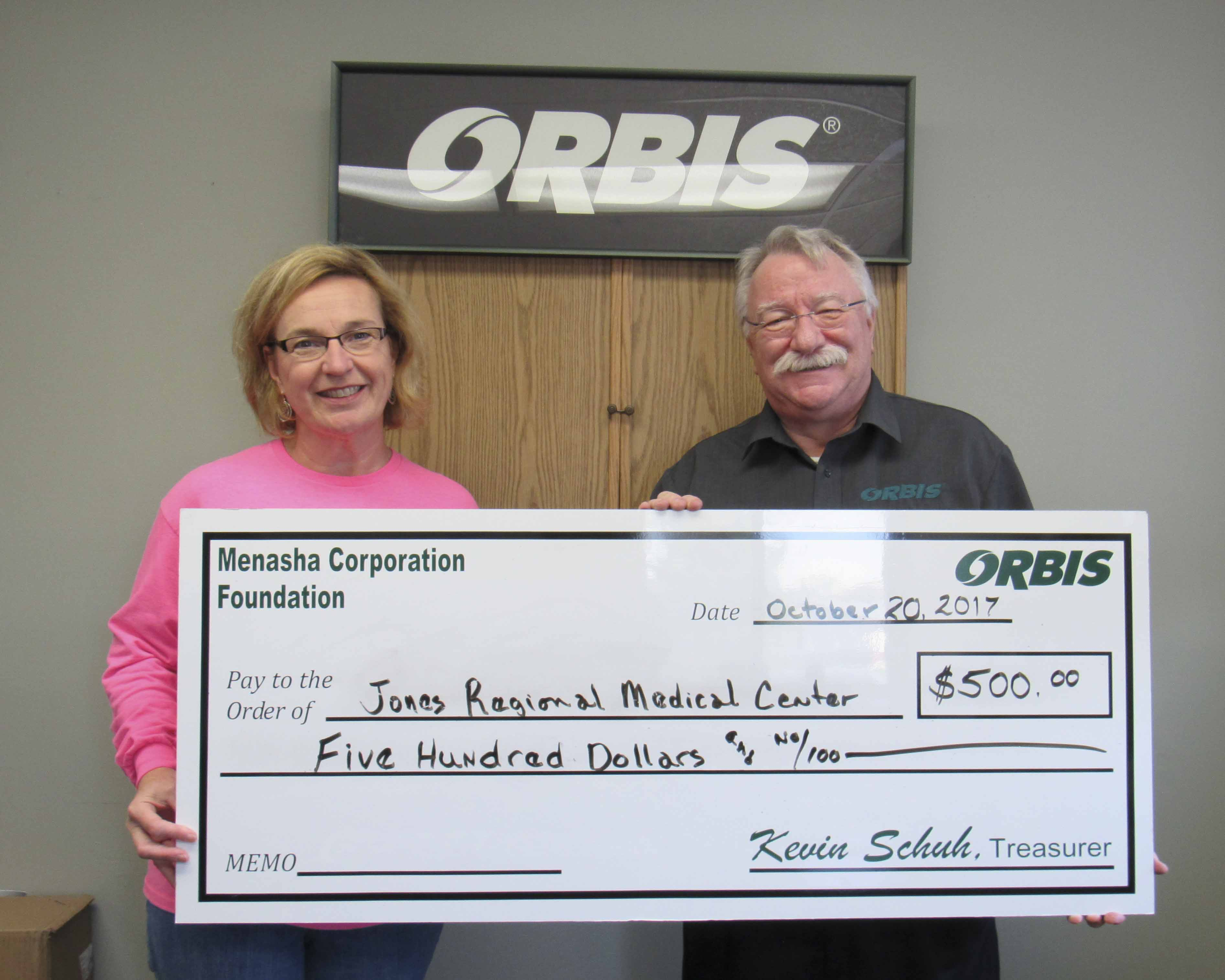 Sheila Tjaden with UnityPoint Health–Jones Regional Medical Center accepts a donation from Richard Talcott with Orbis. (Photo by Kim Brooks)