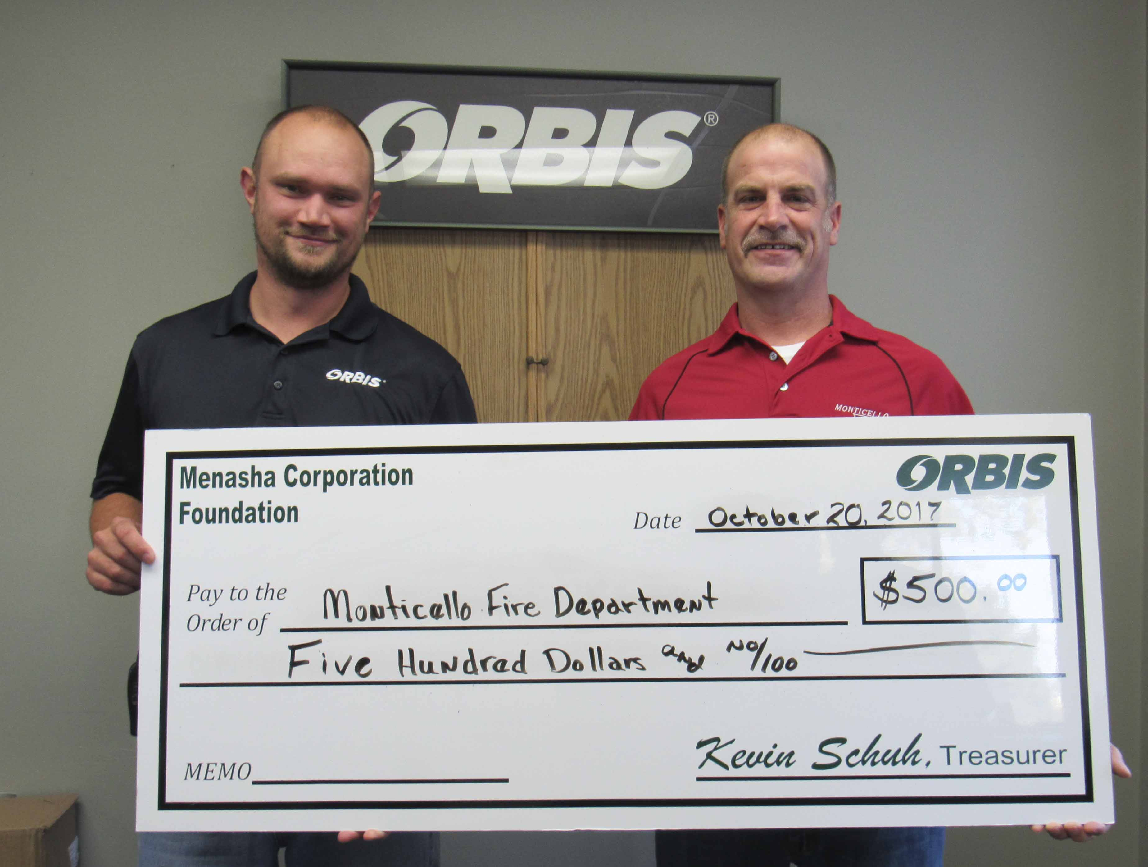Greg Kemp (left) with Orbis presents a check to Don McCarthy, Monticello Fire Department chief. (Photo by Kim Brooks)