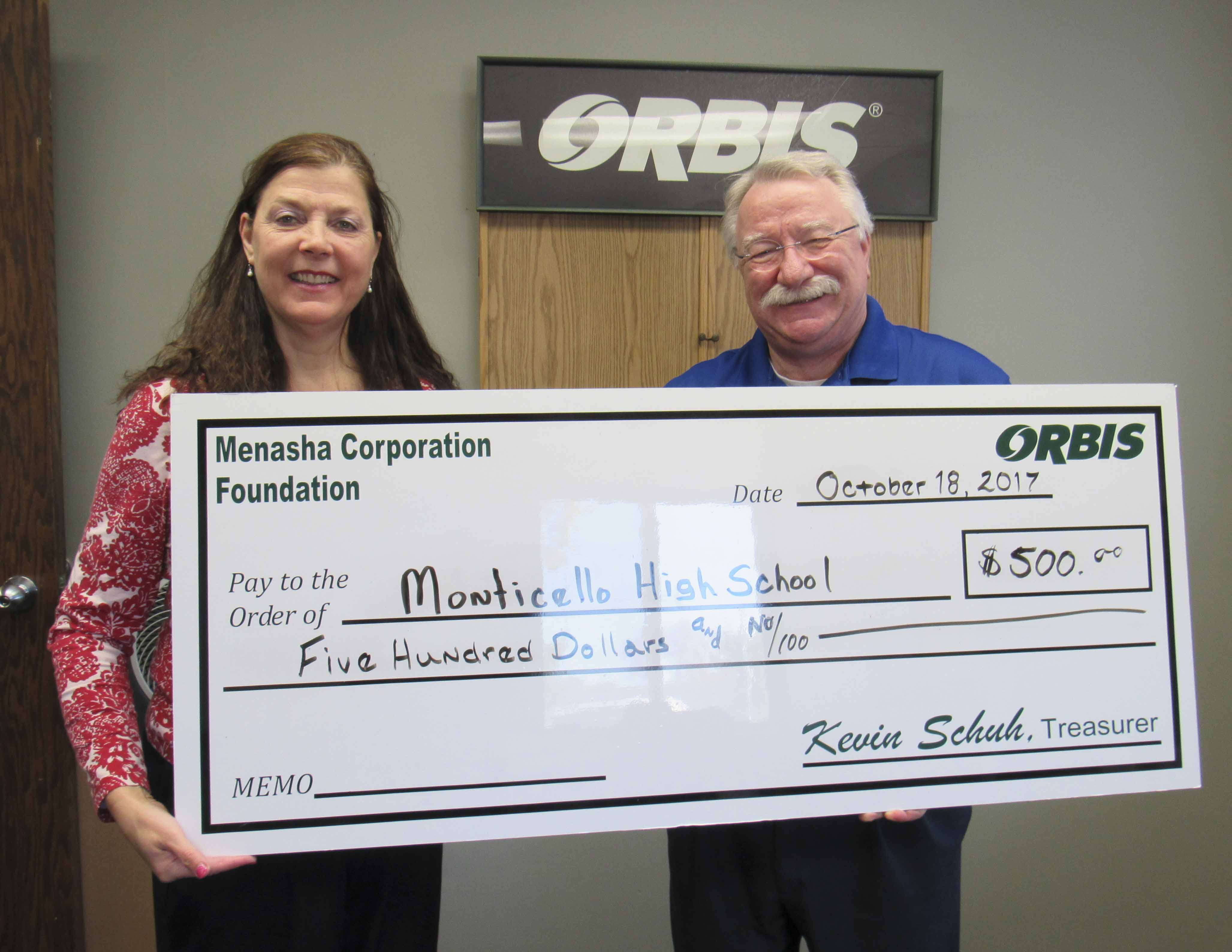 Monticello High School Principal Joan Young accepts a donation from Richard Talcott with Orbis. (Photo by Kim Brooks)