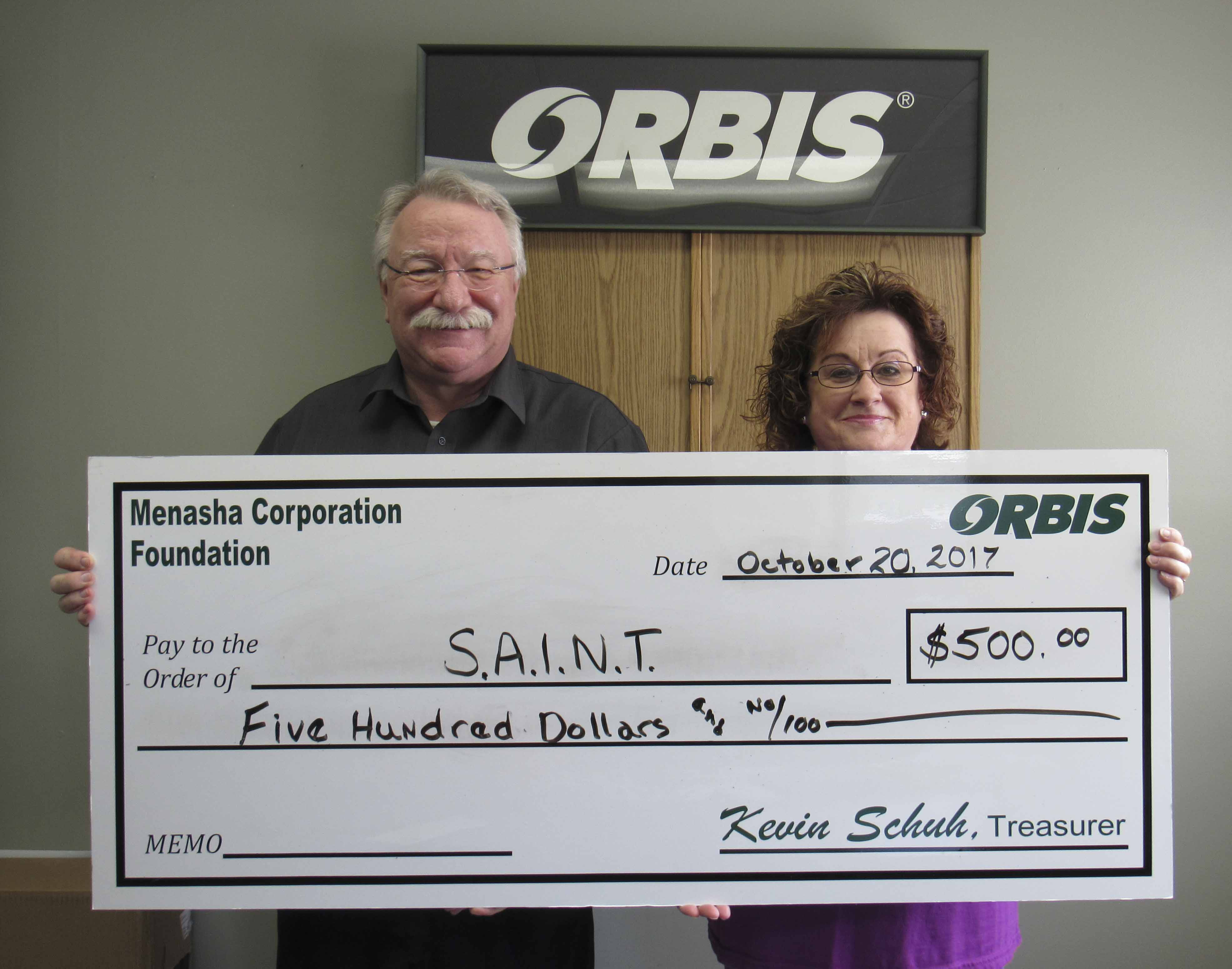 Richard Talcott, representing Orbis, presents a check to Chris O'Clair on behalf of S.A.I.N.T. Cat Adoption Center in Cedar Rapids. (Photo by Kim Brooks)