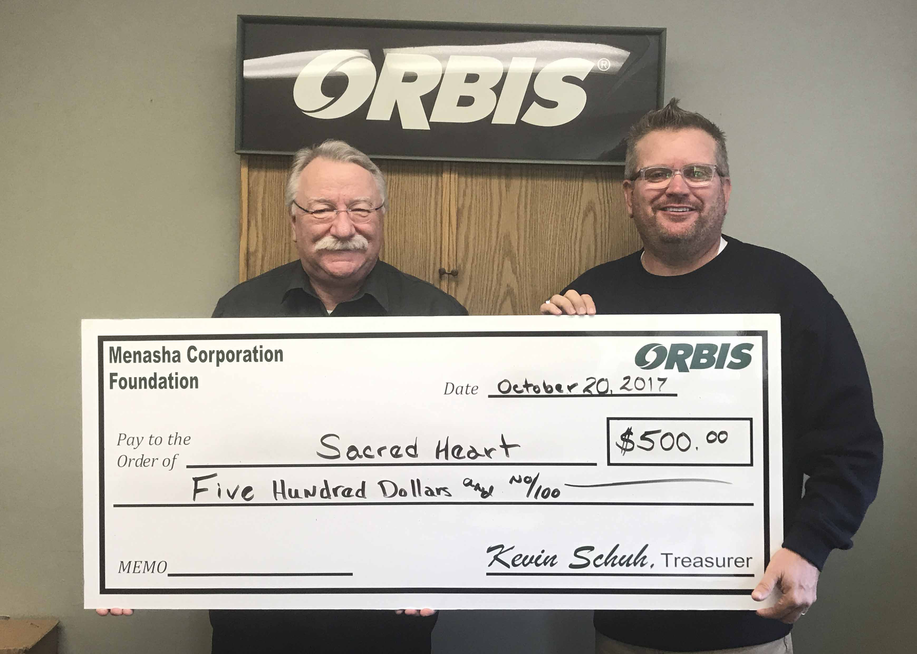 Sacred Heart Catholic School Principal Will Spencer (right) accepts a donation from Richard Talcott with Orbis. (Photo by Mary Yanda)