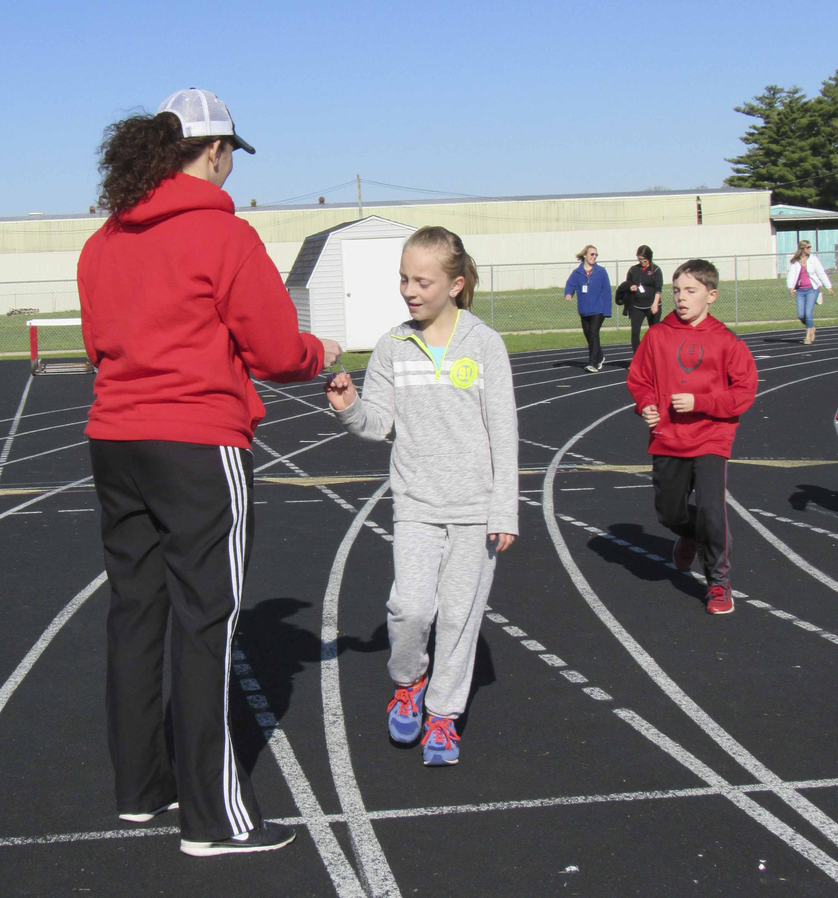 Andrea Giegerich and Kyle Arduser approach the start/finish line as they collect a bracelet from PTO volunteer Jessica Hansen. Each student received one bracelet after each lap. The students averaged 10-12 laps at the end of the hour. The bracelets were donated by PTO. Water and cheese sticks were donated by Culligan and the Jones County Dairy Producers.