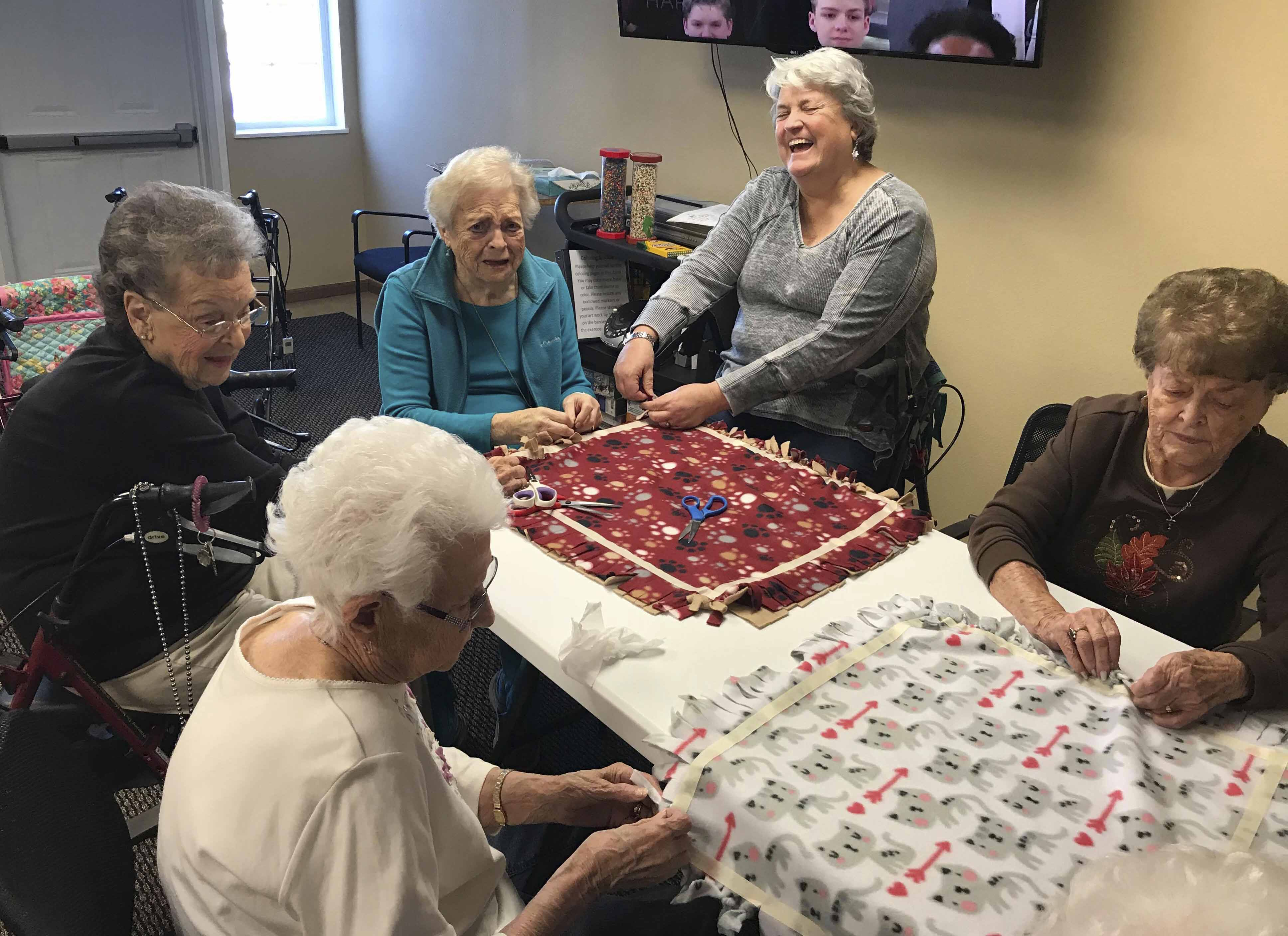 Tenants and family members work on cutting and tying fleece blankets for the dogs and cats at the AWF shelter in Monticello. Clockwise from bottom left are Doris Husmann, June Zirkelbach, Rosemary Welter, Welter's daughter Melinda Pyde, and Mary Jo Lorenzen.