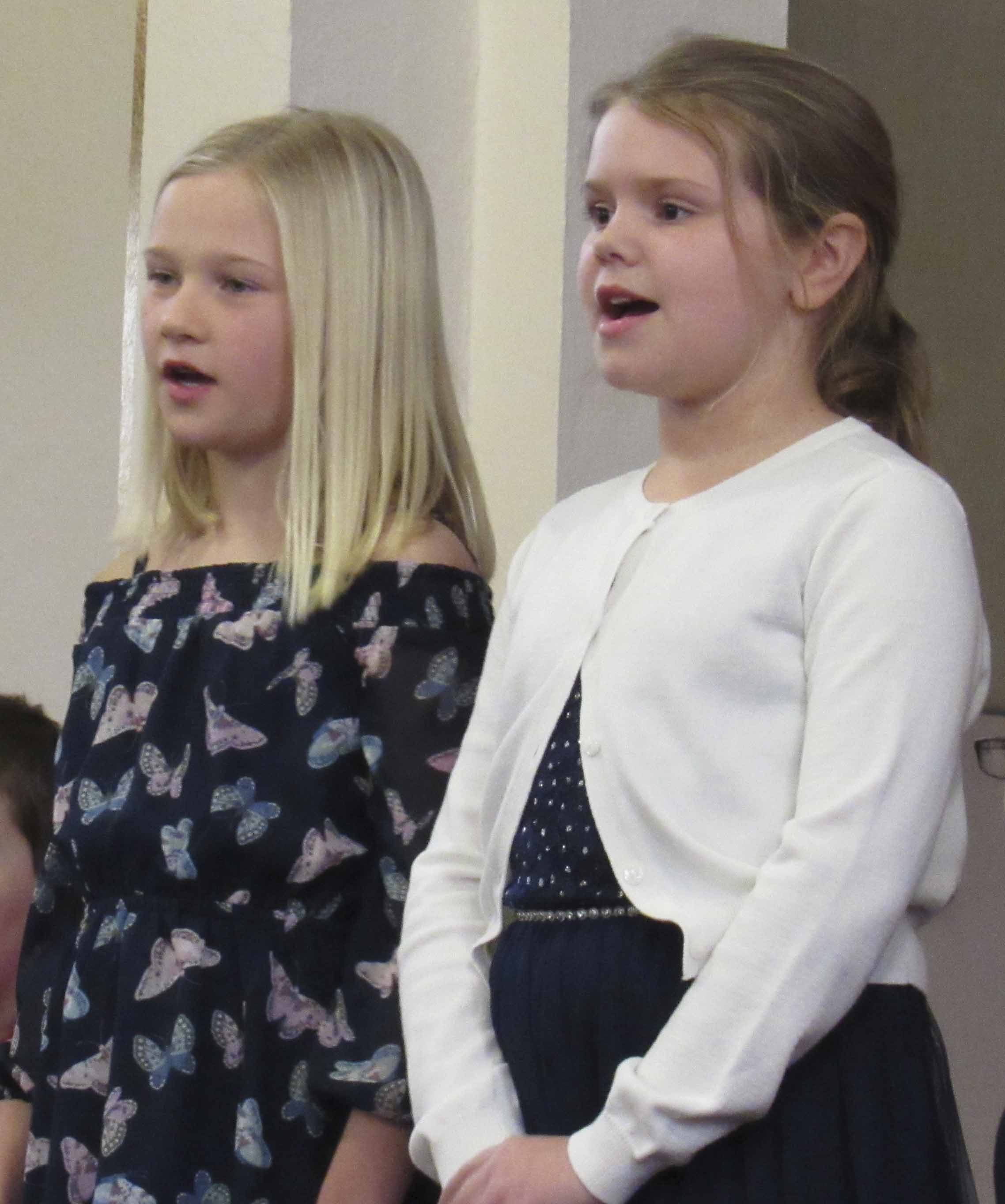"Halle Recker and Leah Schemmel, both fourth-graders at Sacred Heart School, sing during their opening number, ""Rockin' All Night."""