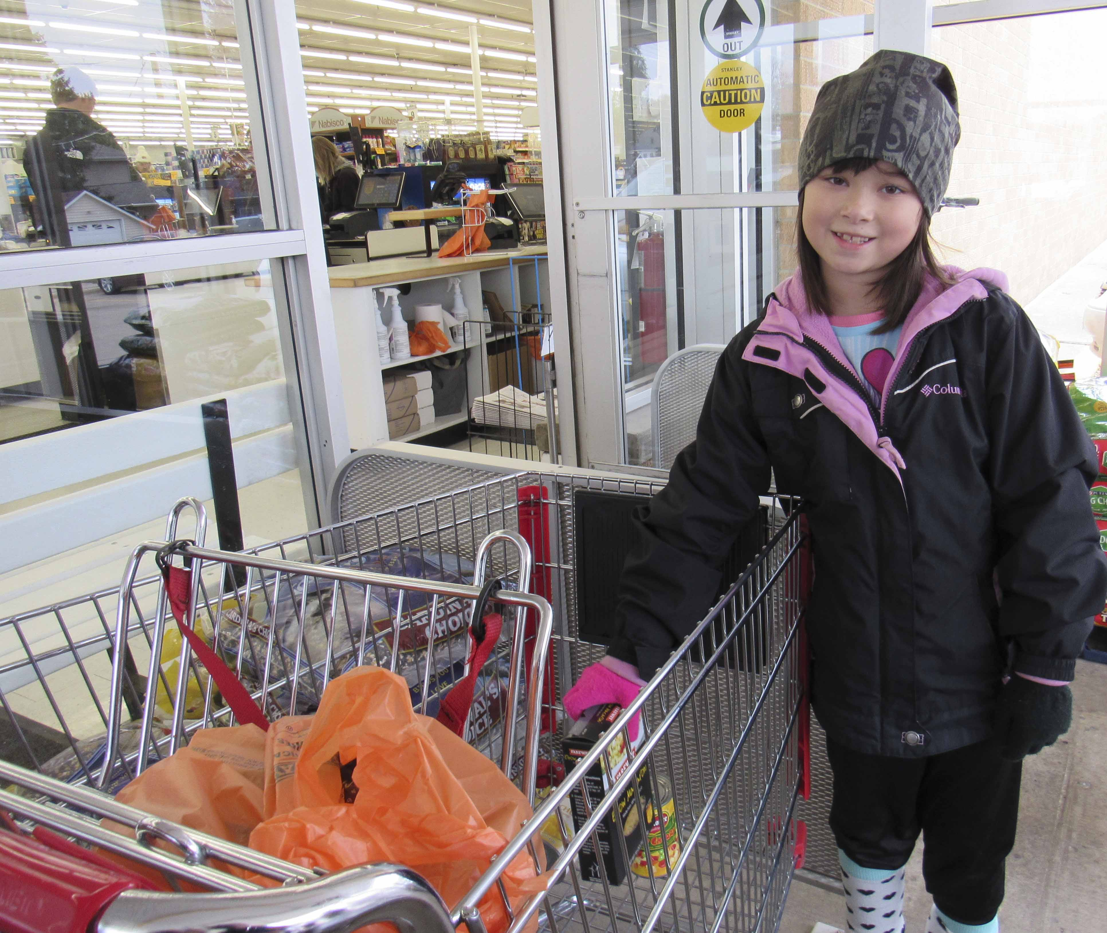 Keira Lee of Monticello donates a box of noodles to the Senior Dining fundraiser. Volunteers and Senior Dining staff were present at both the Monticello and Anamosa Fareway Stores collecting donations for the countywide program. (Photo by Kim Brooks)