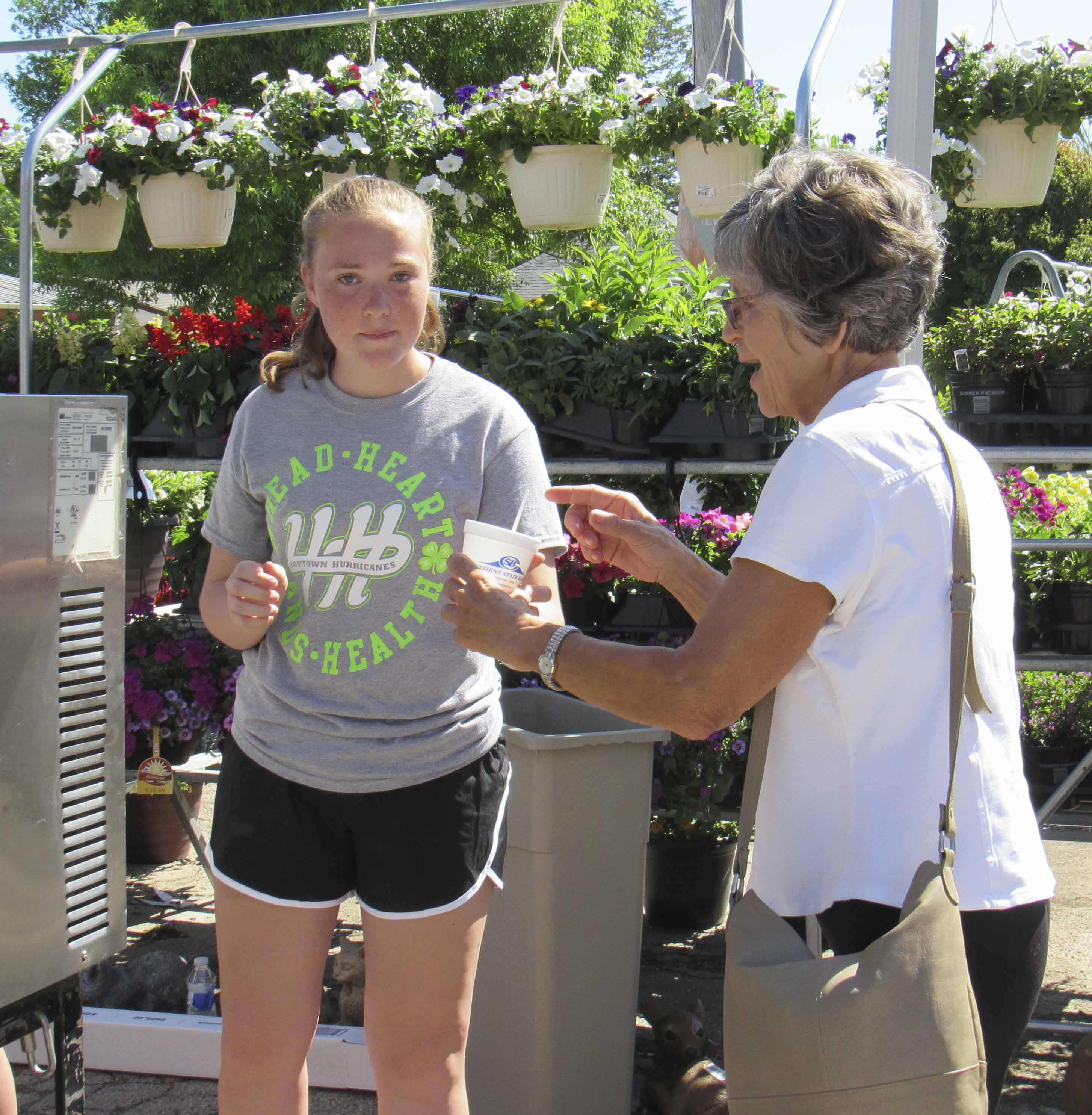 Abbie Sheehy with the Hopkinton Hurricanes 4-H Club passes out free ice cream to those in attendance at the Theisen's Open House. The hot temperatures that morning prompted many to cool off with ice cream.