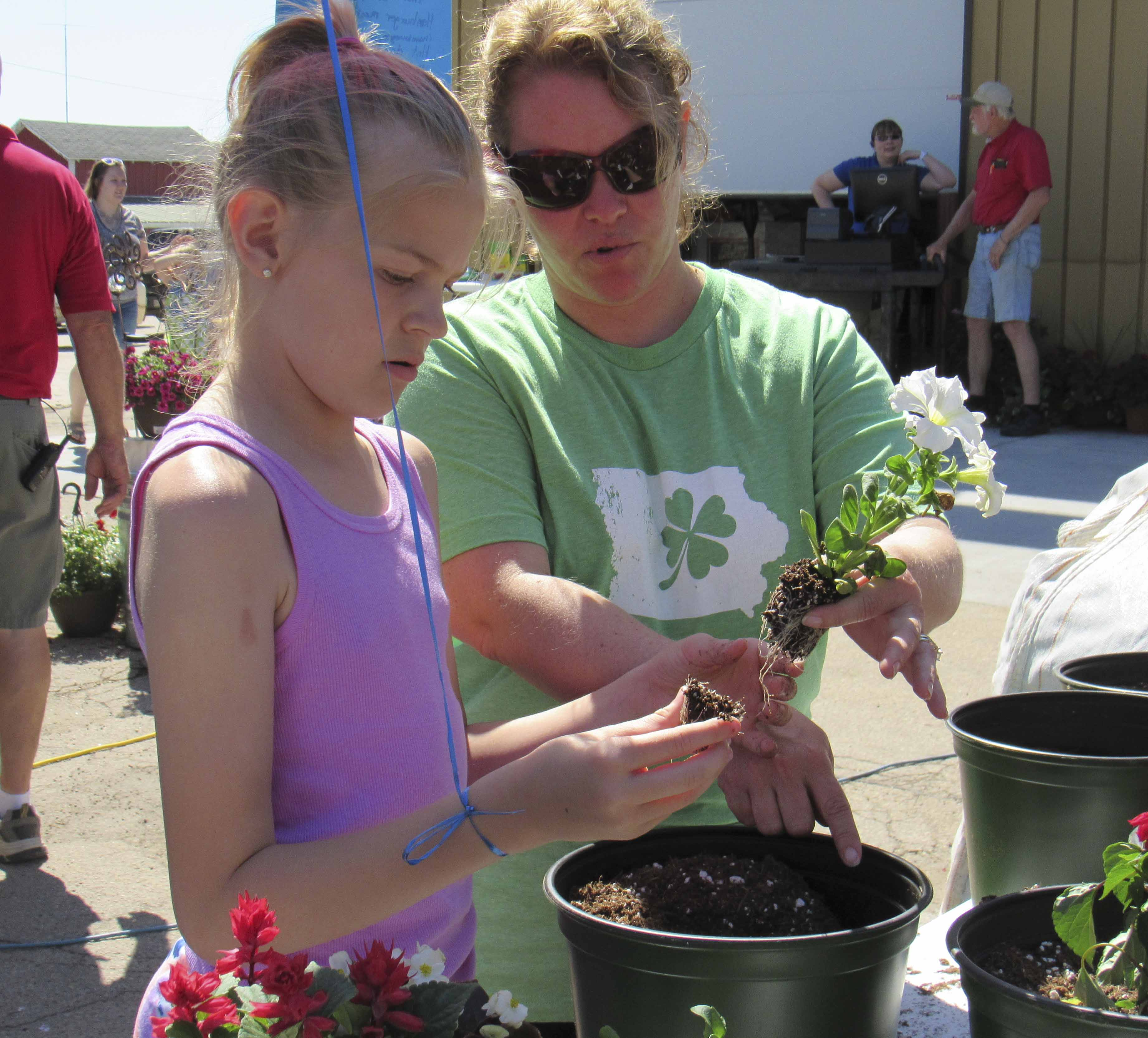 Jessica McElmeel, a parent to a Prairie Hill 4-H member, assisted DeeAnna Pumphrey in planting flowers. The planting demonstration was also free during the Theisen's Open House event.