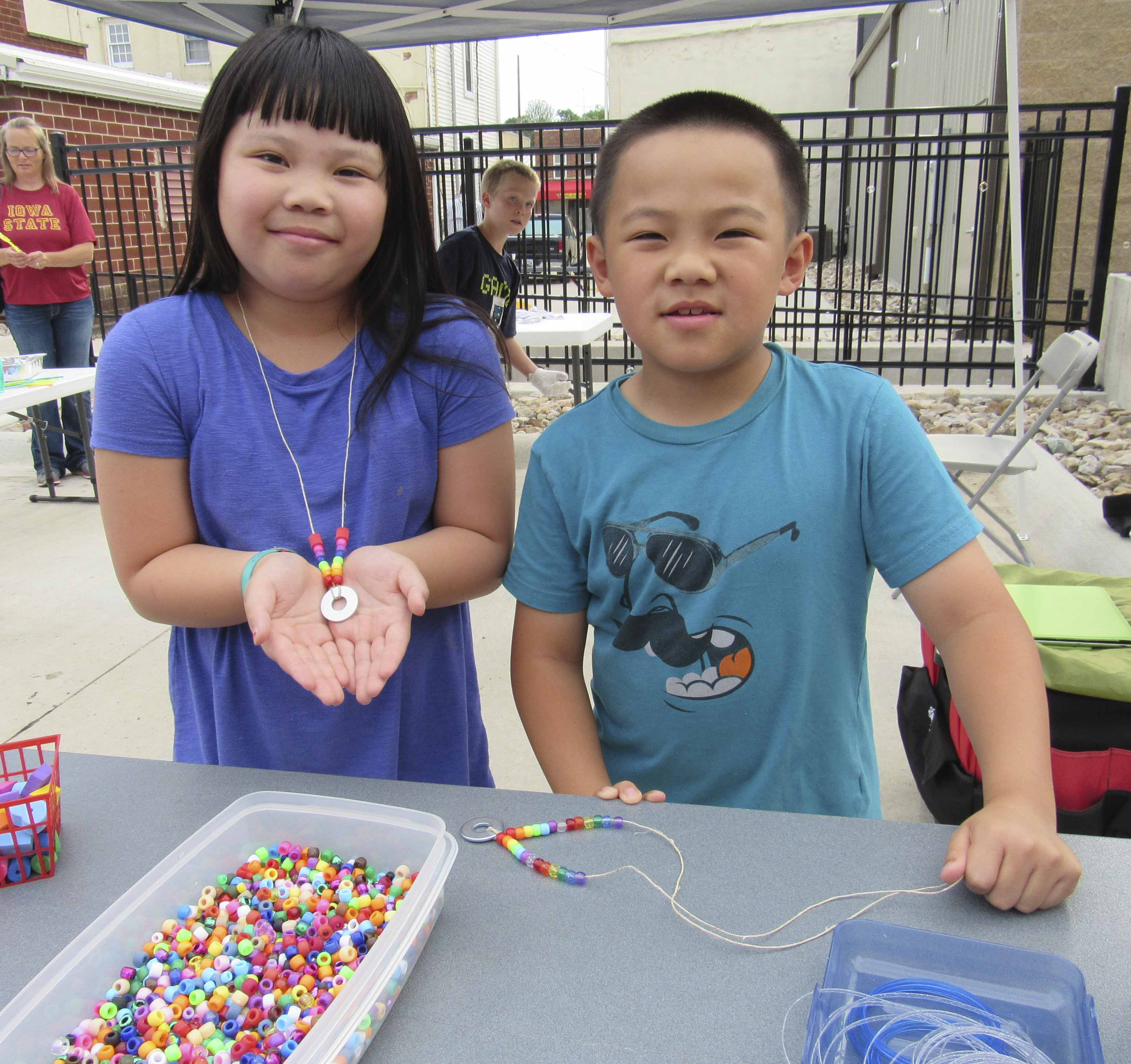 Bonnie and Ethan Tran of Monticello show off their washer and bead necklaces they made at Uptown Thursday Night. The crafts were courtesy of the Monticello Public Library.