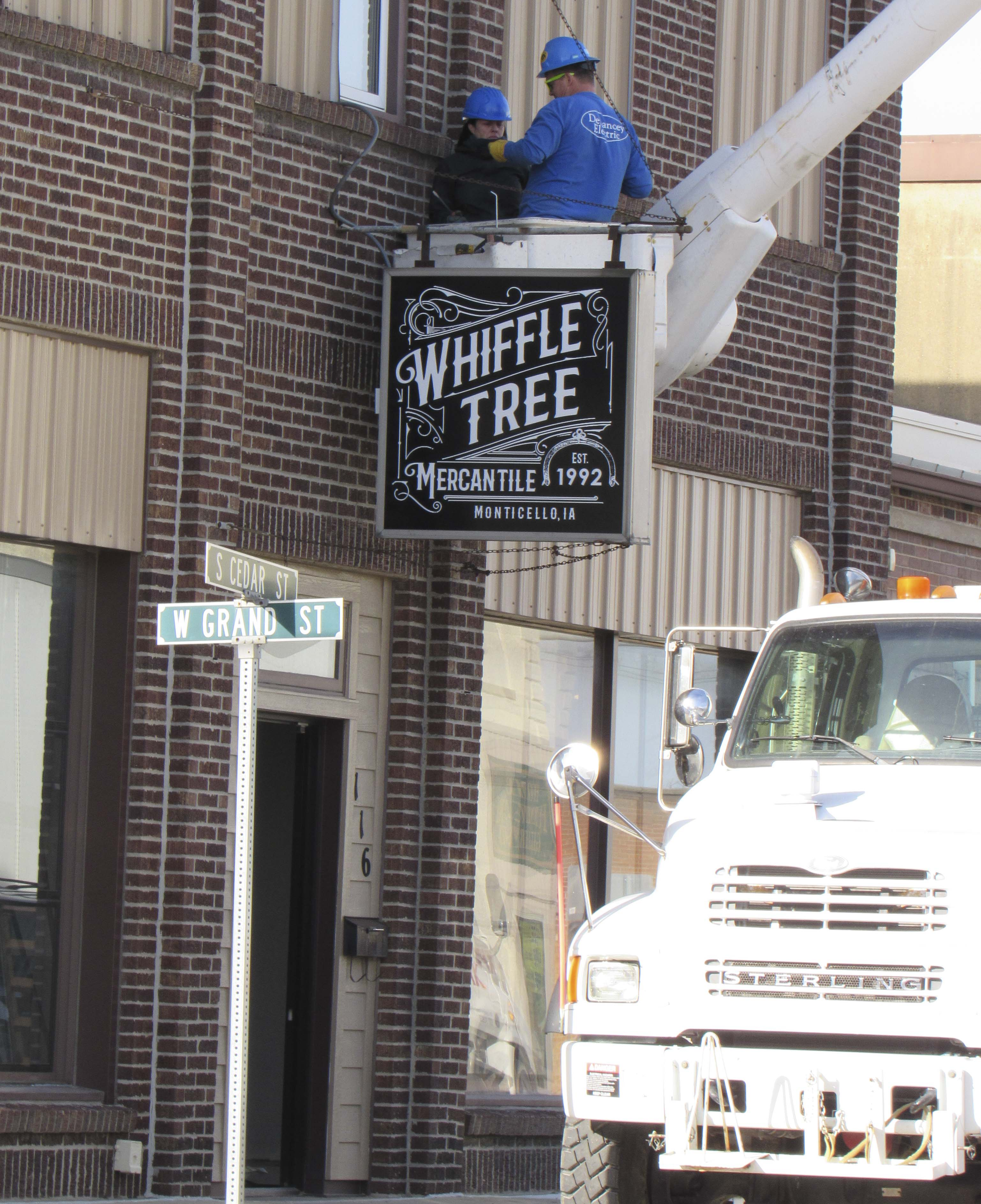 DeLancey Electric in Anamosa installs the new sign outside of Whiffle Tree Mercantile in downtown Monticello. The long-time business owned by Leroy Mootz was recently purchased by Bobby Krum of Amber. The building is currently undergoing some extensive renovations before it reopens to the public. (Photo by Kim Brooks)