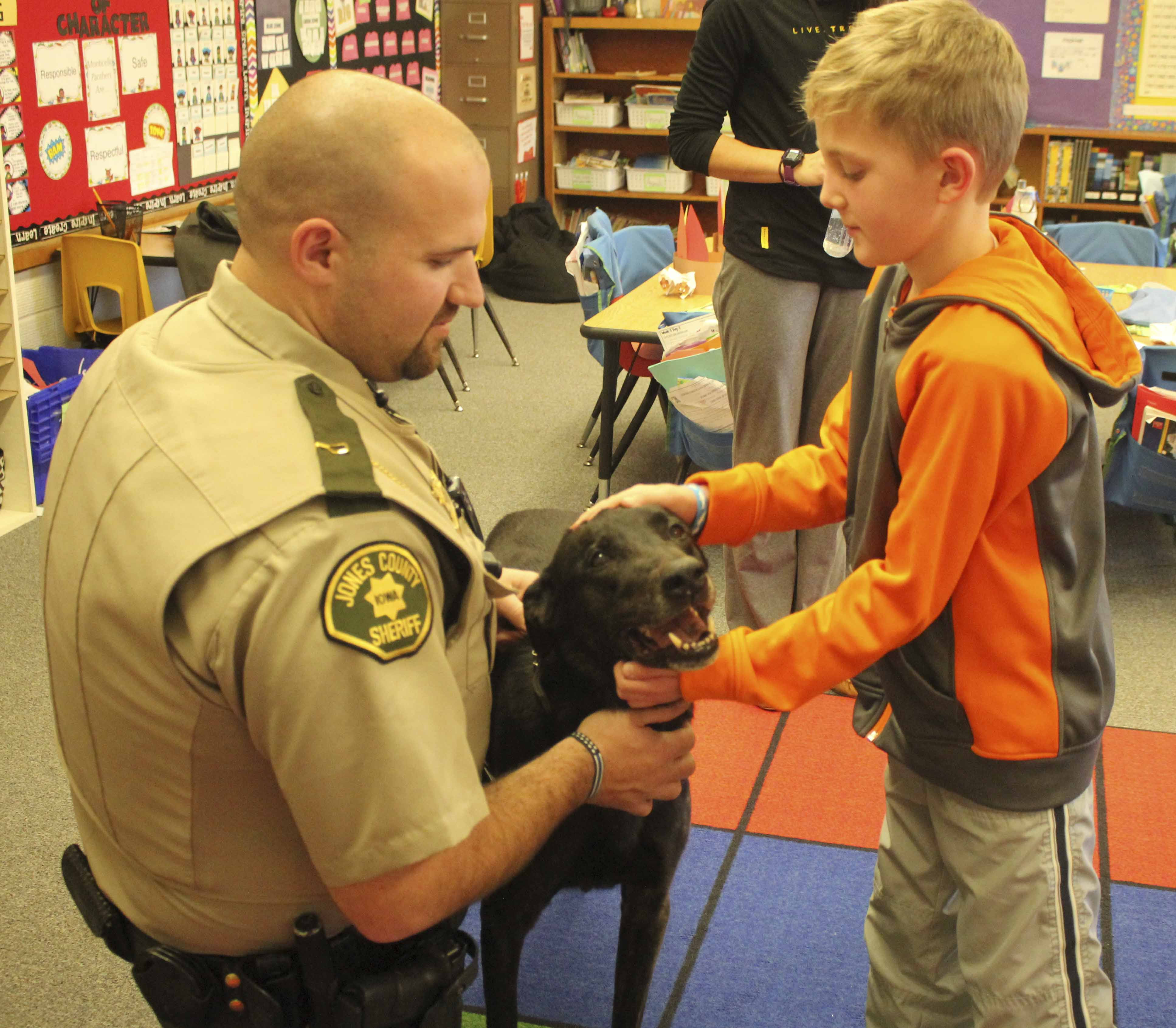 Carpenter Elementary School second-grader MacKendrick Burkle pets Loki, the K-9 dog who visited the school Nov. 21 with Jones County Sheriff's Deputy Derek Denniston. The class had been reading a book about a police search dog, and for the students' Panther Paw reward, they voted to have Loki visit. (Photos by Pete Temple)
