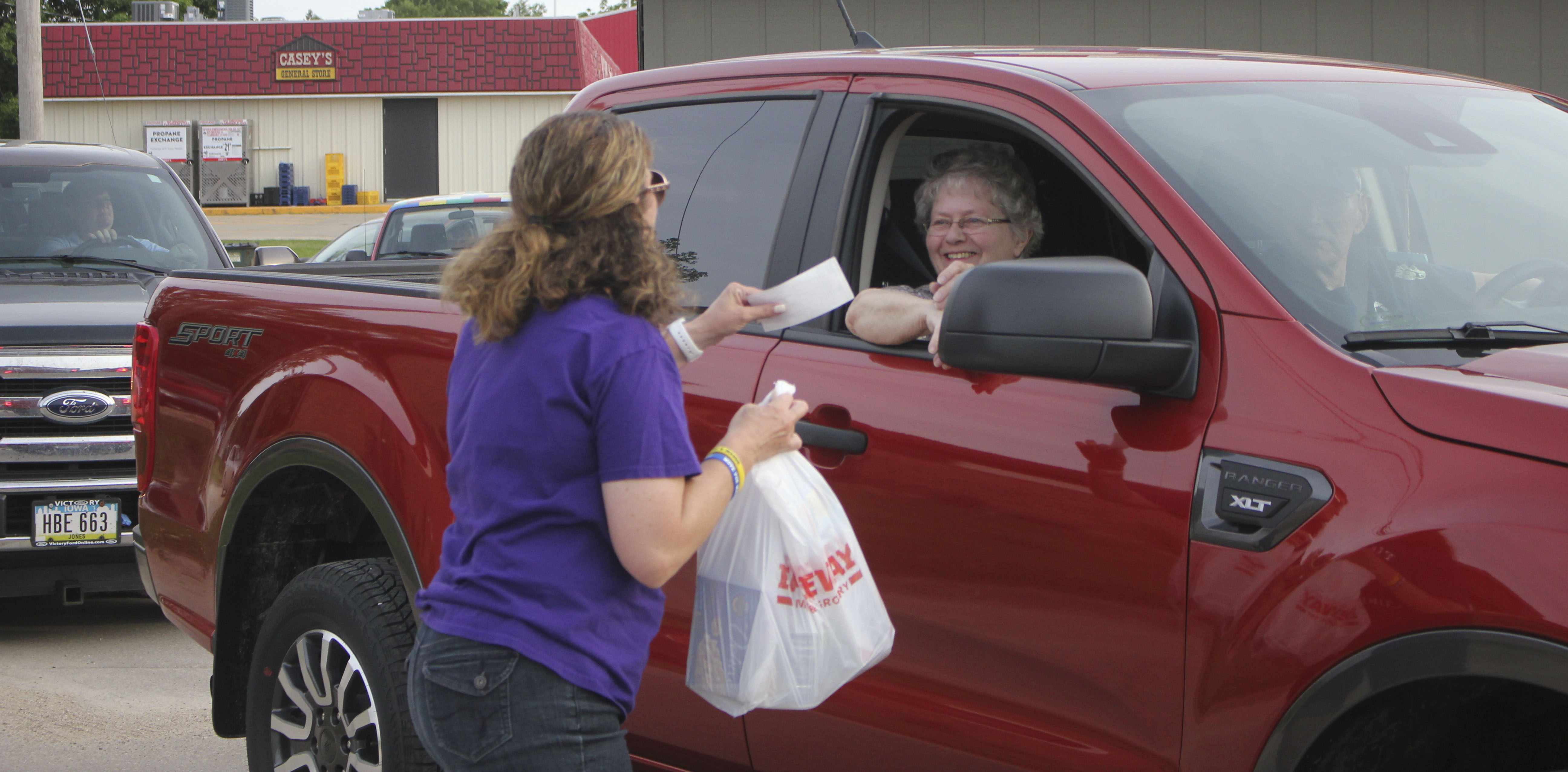 Phyllis Tapken (in vehicle) makes a donation, collected by Carrie Manternach, during the Saturday night cruise night June 6 in Monticello. Vehicles cruised the loop between Diamond Pi and Regions Bank. The event totaled $649 in donations for Jones County Relay for Life, as well as many goods for the Monticello Food Pantry. (Photos by Pete Temple)