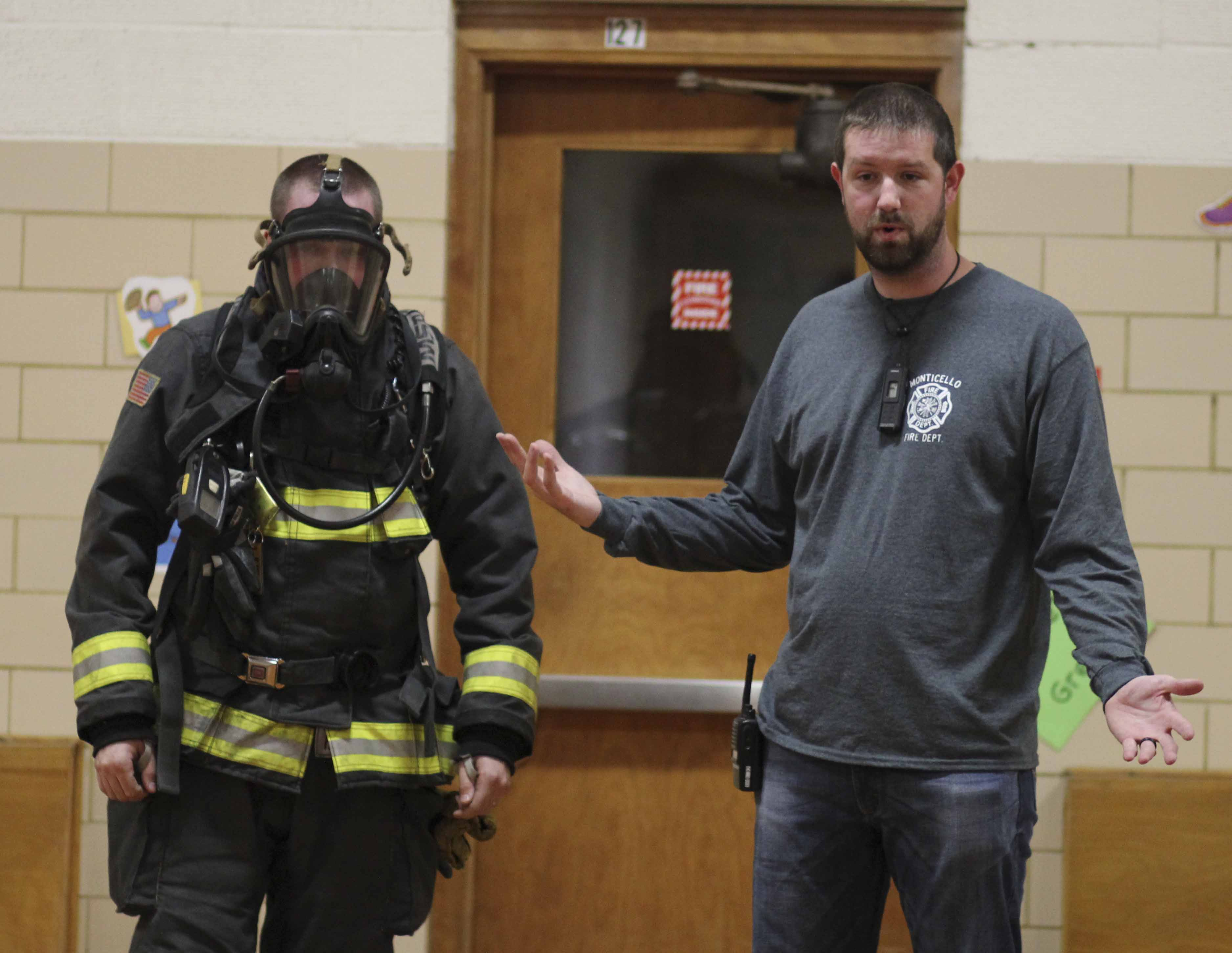 Firefighter David Husmann speaks to Carpenter students about fire safety, as Cody Miles (left) displays the necessary gear Oct. 13.