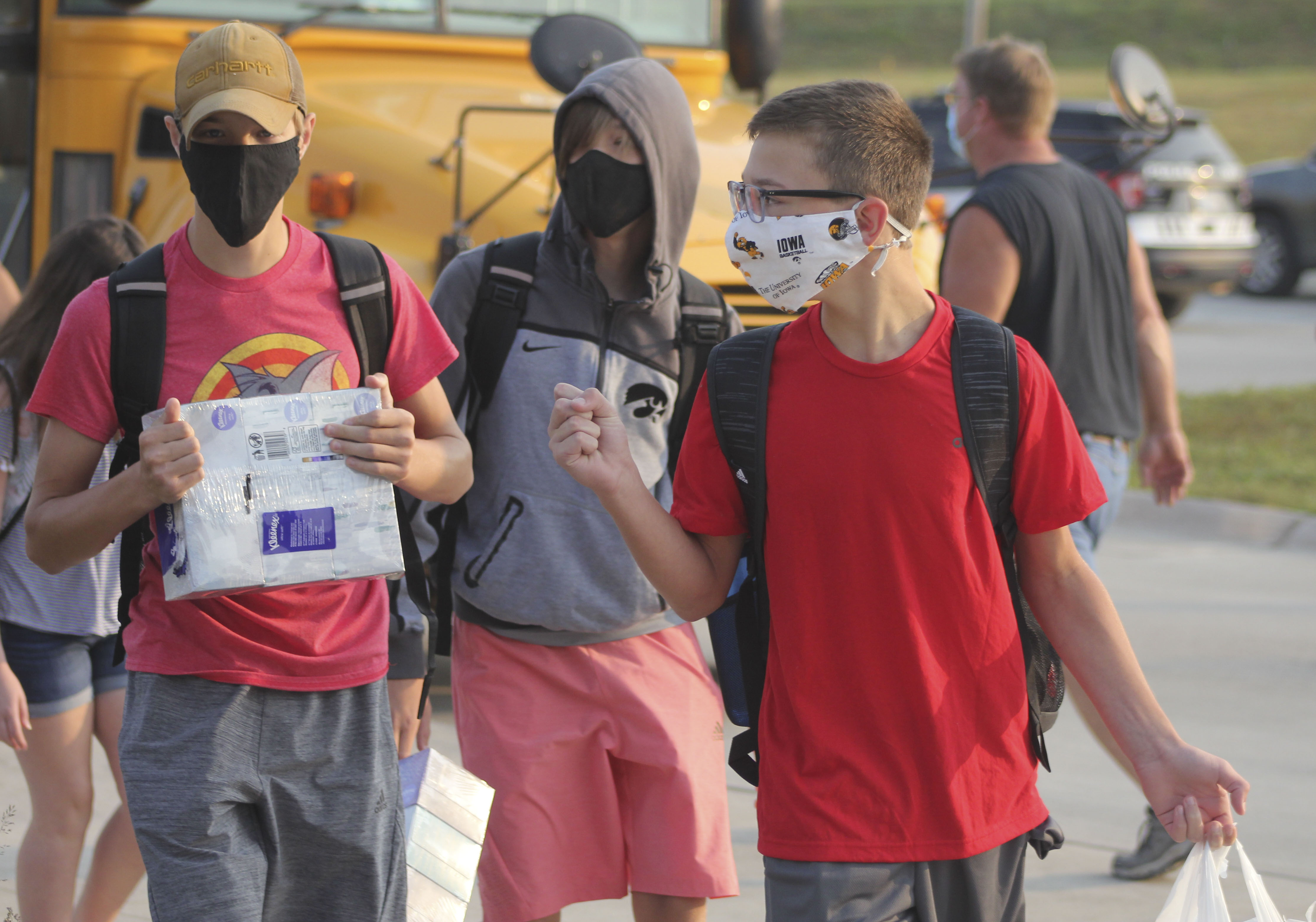 Masked middle school students (from left) Connor Eastin, Tyler Eastin and Gatlin Wright make conversation while approaching the new middle school building Monday. More first day of school photos on A18. (Photo by Pete Temple)