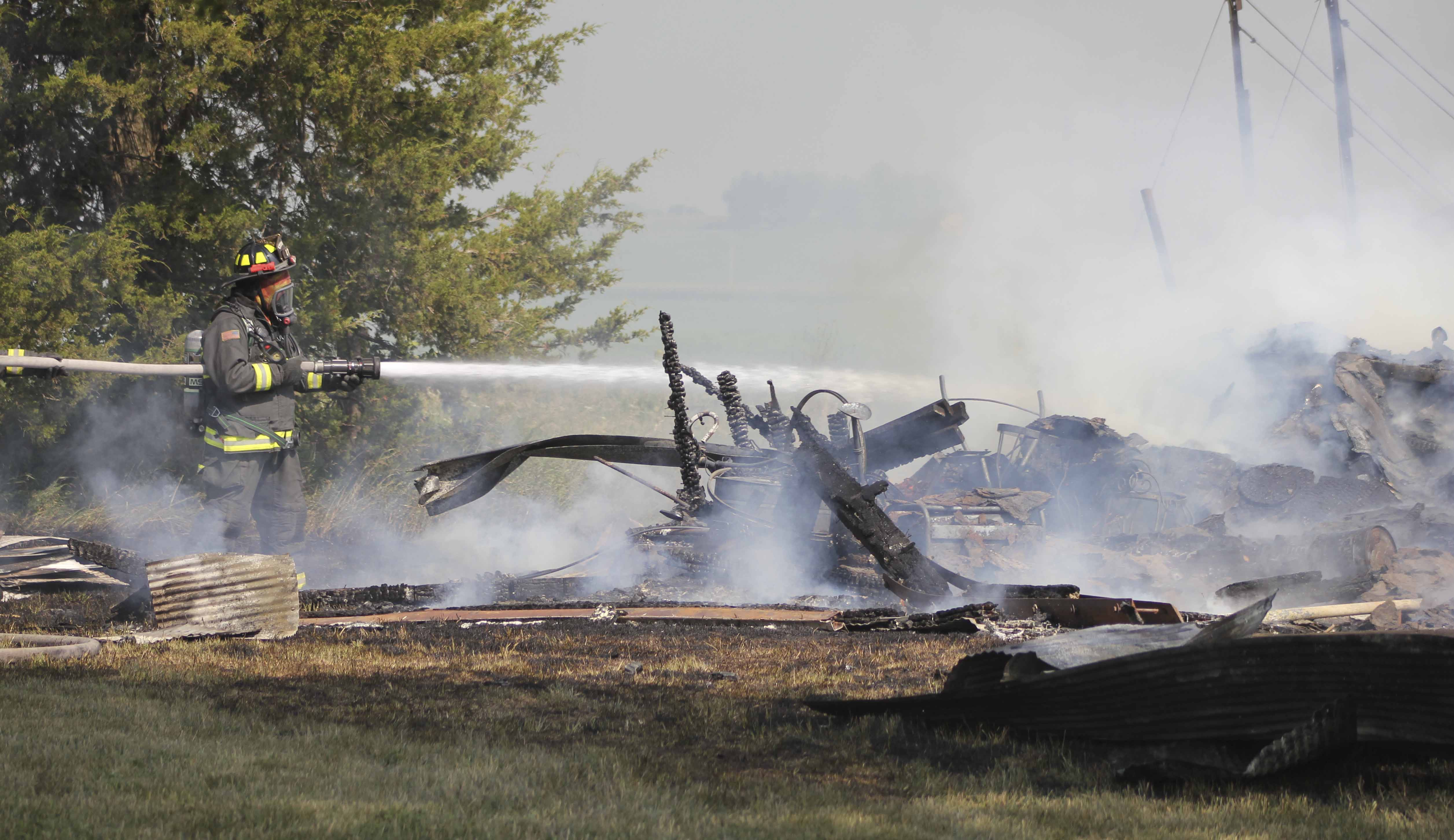 Firefighter Tim Miles works to put out the flames at the Helgens farm. (Photo by Pete Temple)