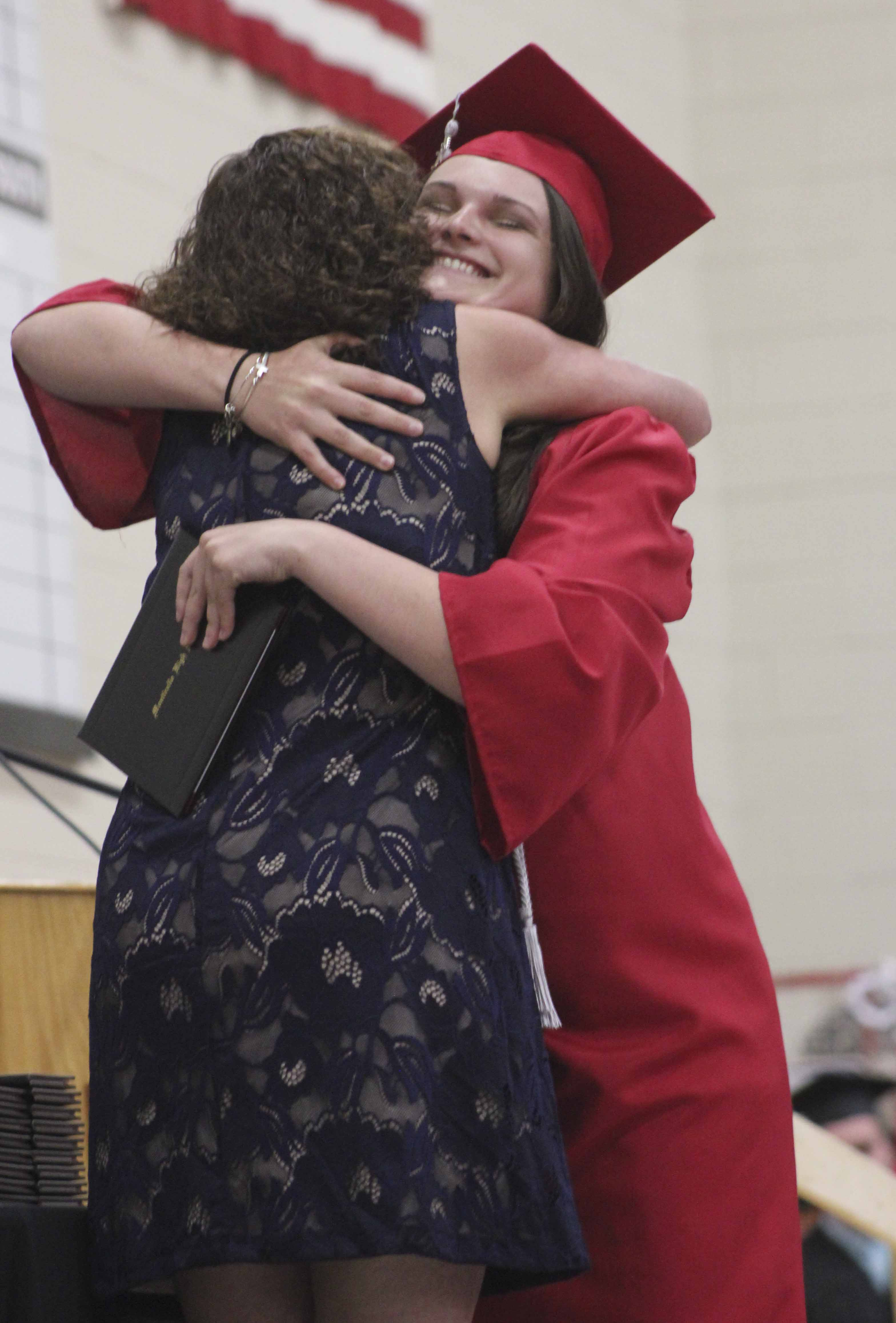 Graduate Riley Melchert gets a hug from Monticello School Board president Angie Beitz after Melchert received her diploma. As a small child, Melchert went to Beitz for daycare.