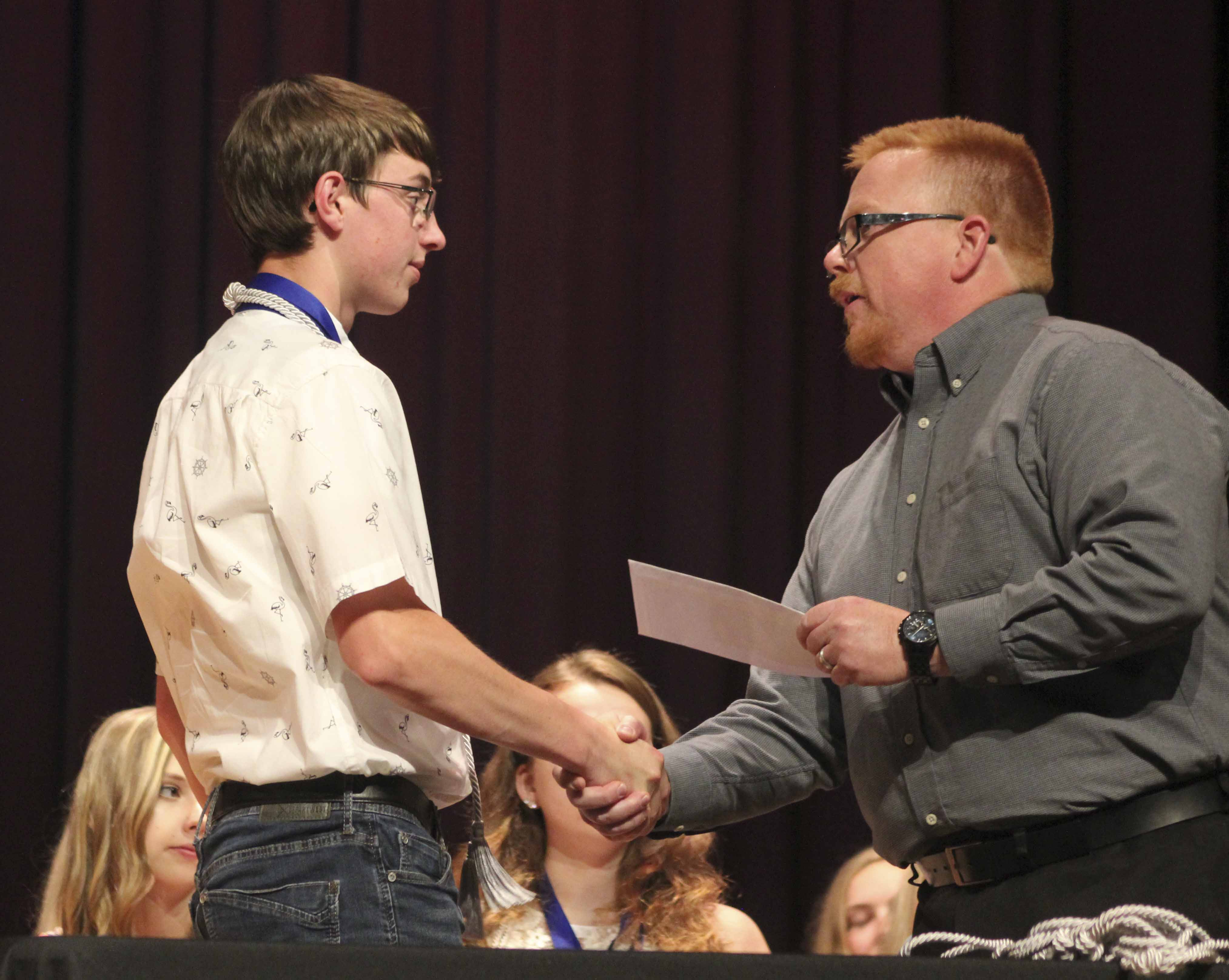 Monticello High School seniors received dozens of scholarships during Honors Night, held May 22 in the MHS Auditorium. Senior Ben Barnhart accepts a Monticello Veterans Organizations Memorial Scholarship from Doug Bean. (Photos by Pete Temple)