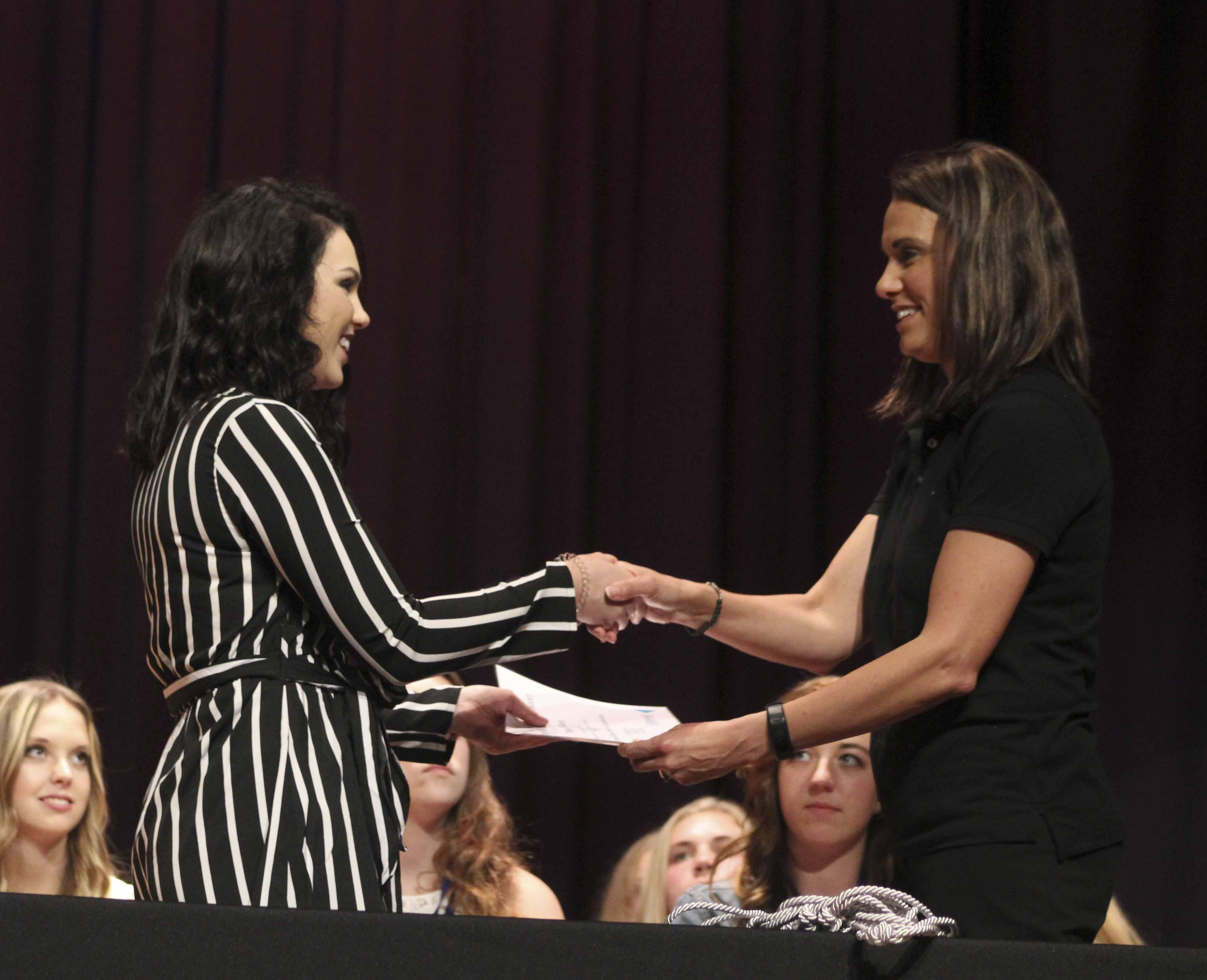 Paige Folken (left) receives a scholarship certificate from Julie Welter of the Jones Regional Education Center (Kirkwood).