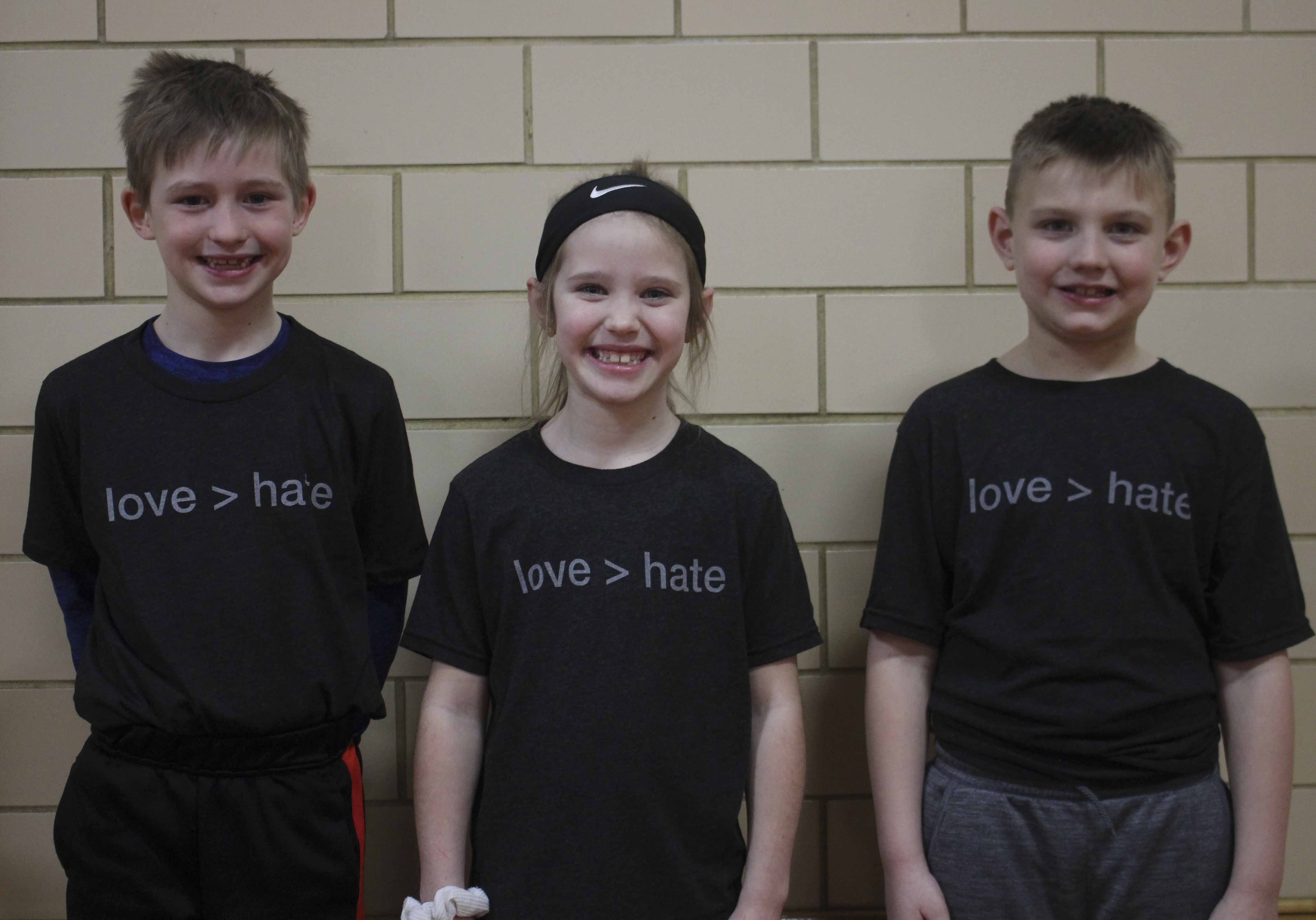 Displaying their Love > Hate t-shirts, from left, second-graders Branden Sharlow, Piper Hodge and Drew Manson.