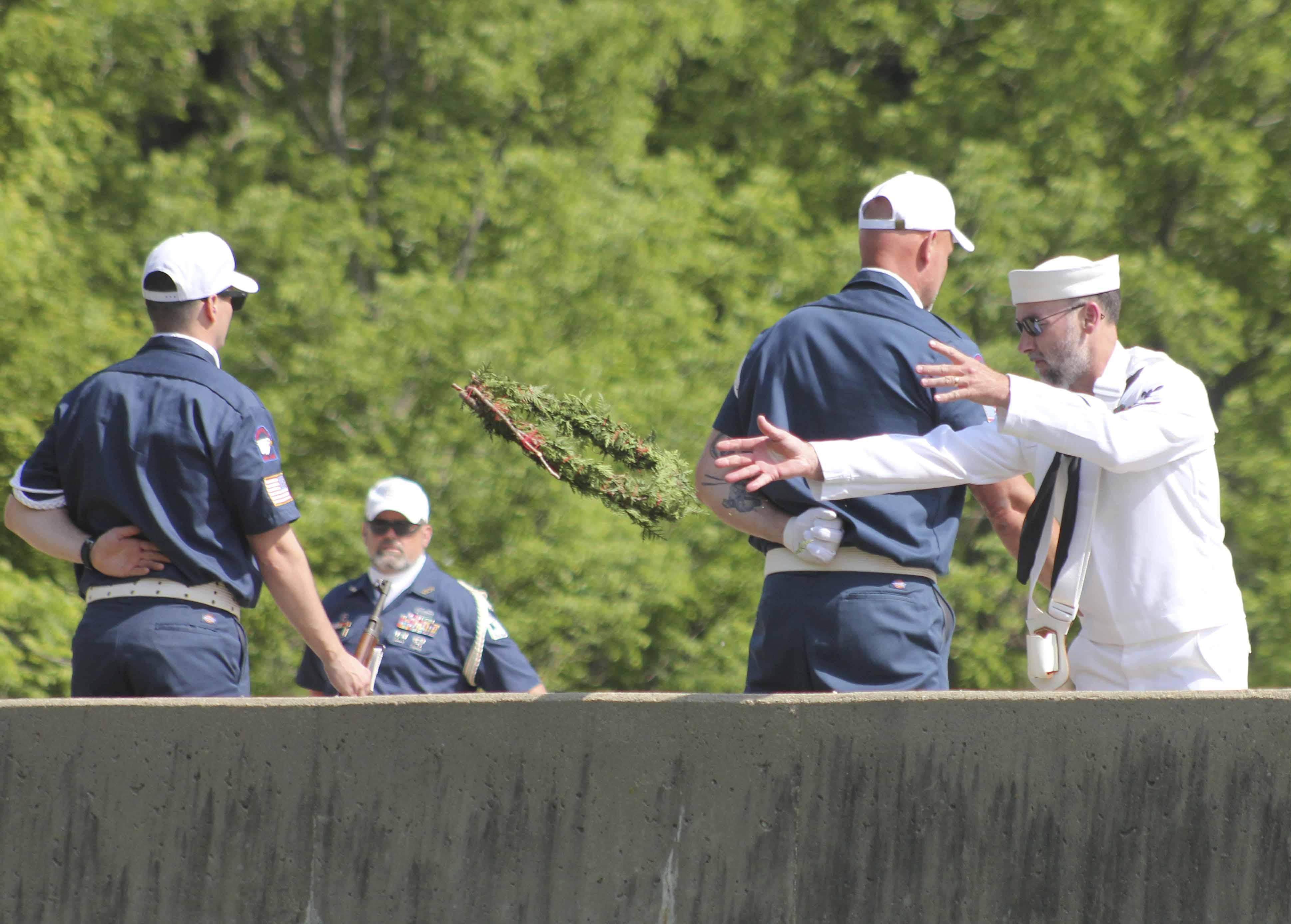 Mike Bachman tosses the wreath into Kitty Creek in memory of U.S. military personnel who were lost at sea. The ceremony was part of the Memorial Day parade.
