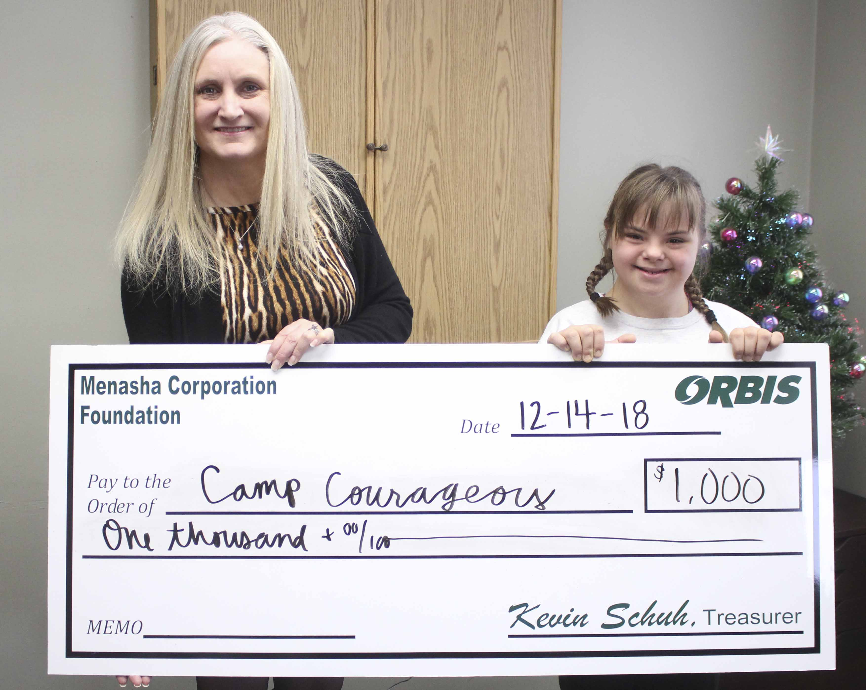 Orbis Corporation of Monticello has made its annual donation to area organizations, including this one to Camp Courageous. Annie Schlarmann (right), representing Camp Courageous, accepts the $1,000 donation from Lynnette Martineau of Orbis. (Photos by Pete Temple)